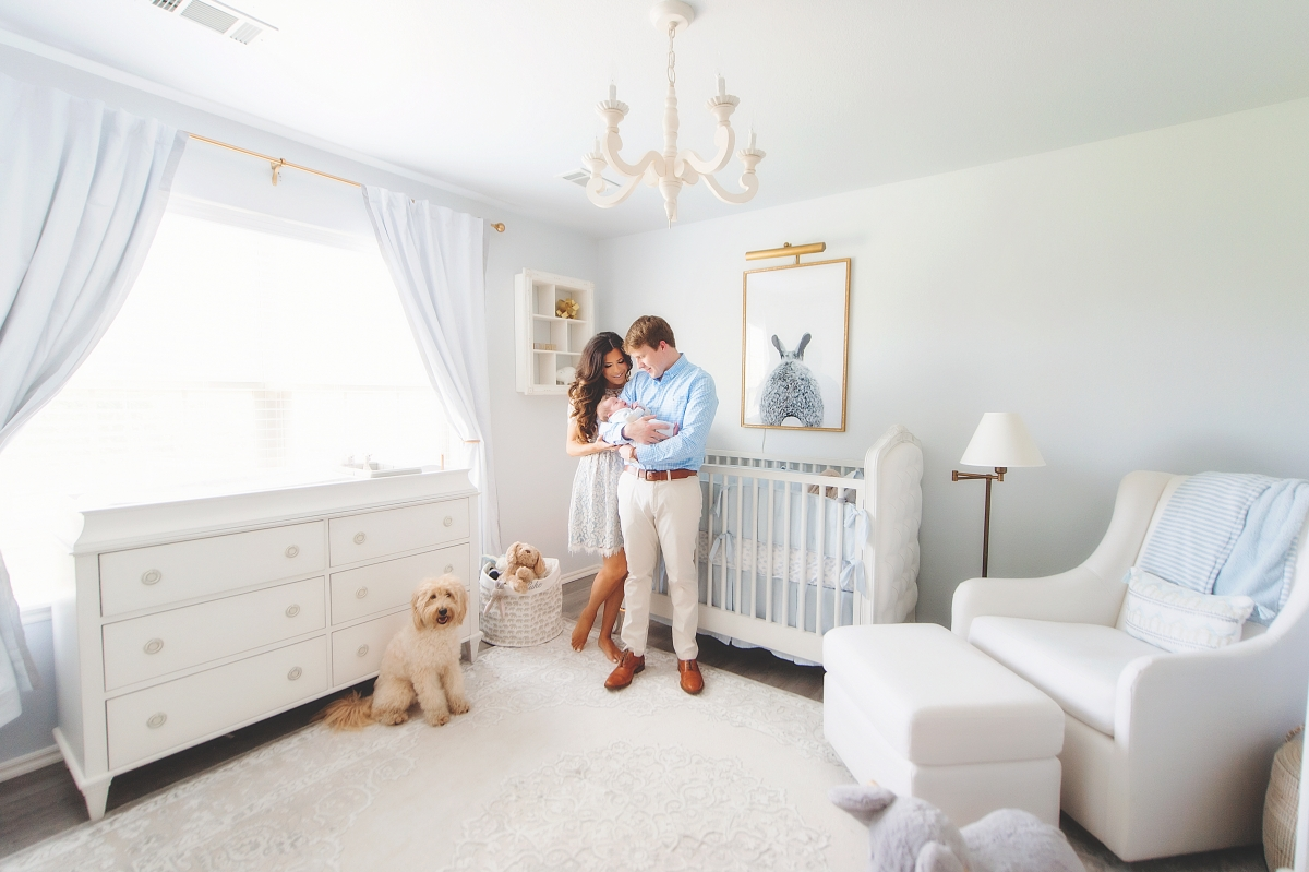 Instagram Recap by popular US life and style blog, The Sweetest Thing: image of Emily Gemma and her husband holding their newborn baby in a nursery with white furniture, white chandelier, black and white bunny print in a gold frame, and a blue and white stripe blanket,