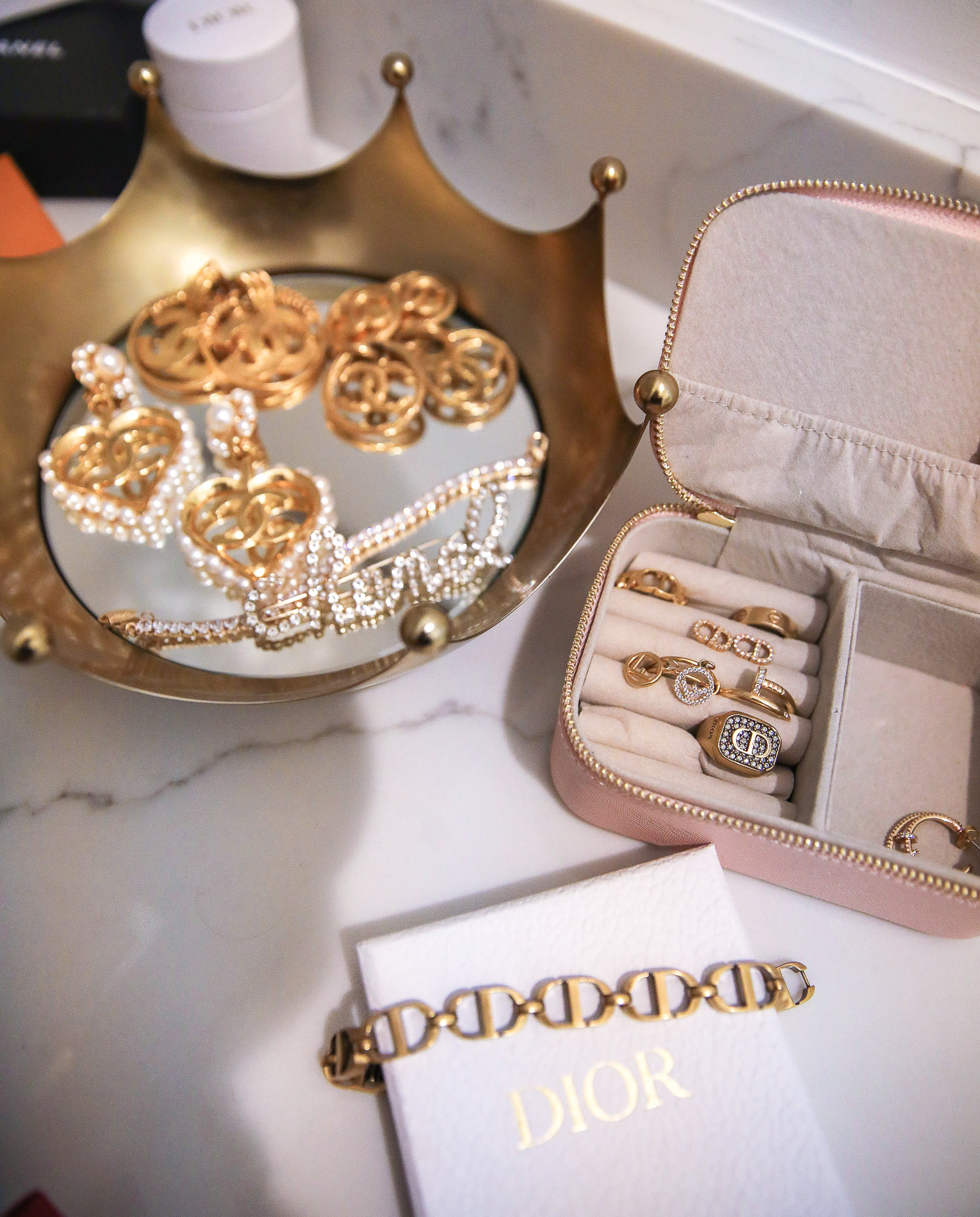 jewelry storage and organization, master bedroom decoration and design, designer jewelry storage | Nighttime Routine by popular US beauty blog, The Sweetest Thing: image of Chanel jewelry in a crown jewelry dish, a Dior bracelet, and Dior and Fendi rings in a pink jewelry case.