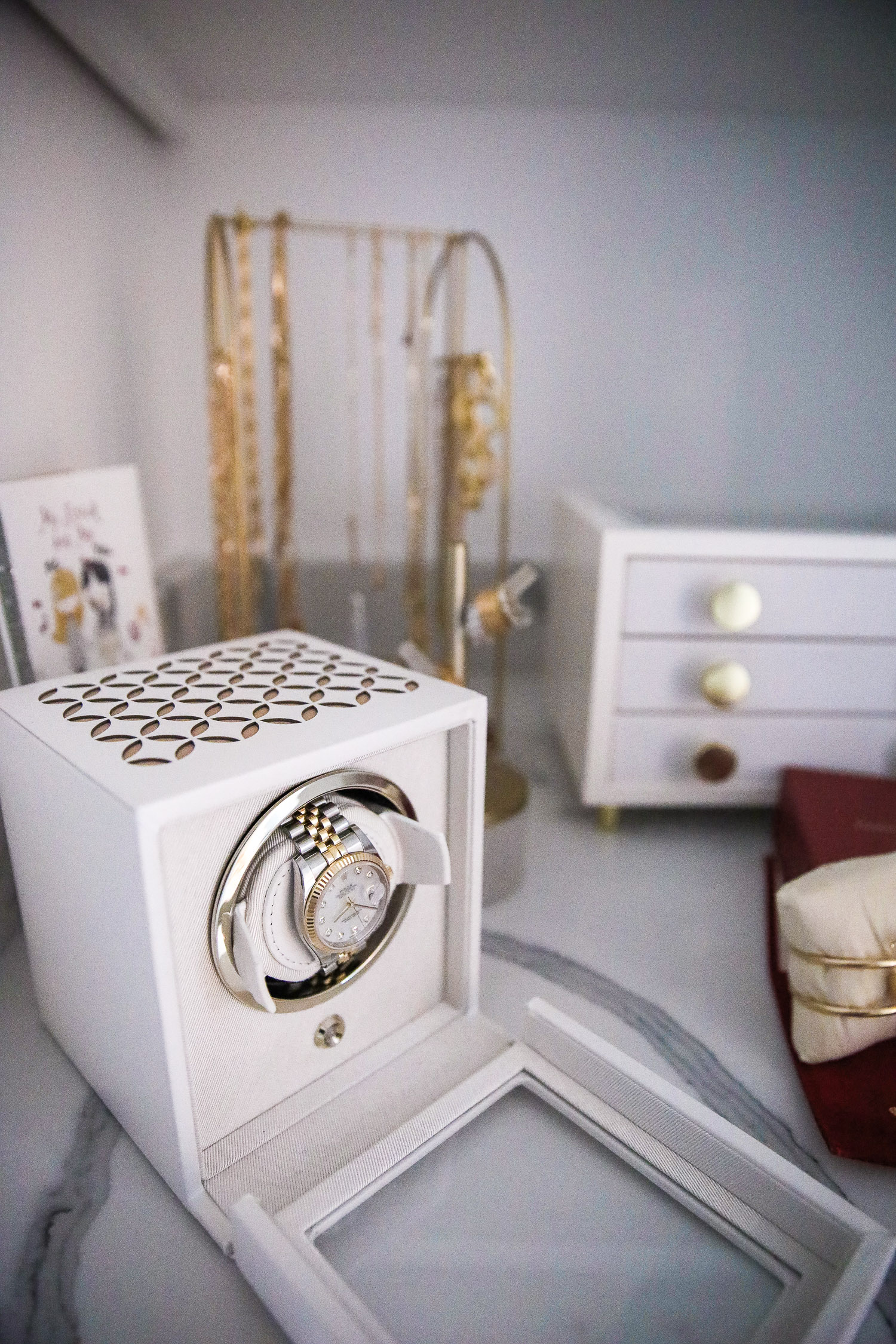 rolex watch winder, white wolf Rolex watch winder, Emily Gemma | Nighttime Routine by popular US beauty blog, The Sweetest Thing: image of a watch winder box, white jewelry box, and gold jewelry rack.