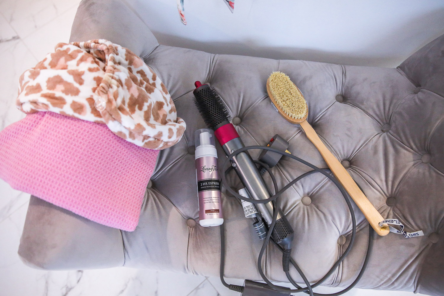 dyson airwrap review, master bathroom white and gold, Emily Gemma | Nighttime Routine by popular US beauty blog, The Sweetest Thing: image of a leopard print body towel, Elemis body exfoliating body brush, and pink textured towel on a grey velvet tuft bench.