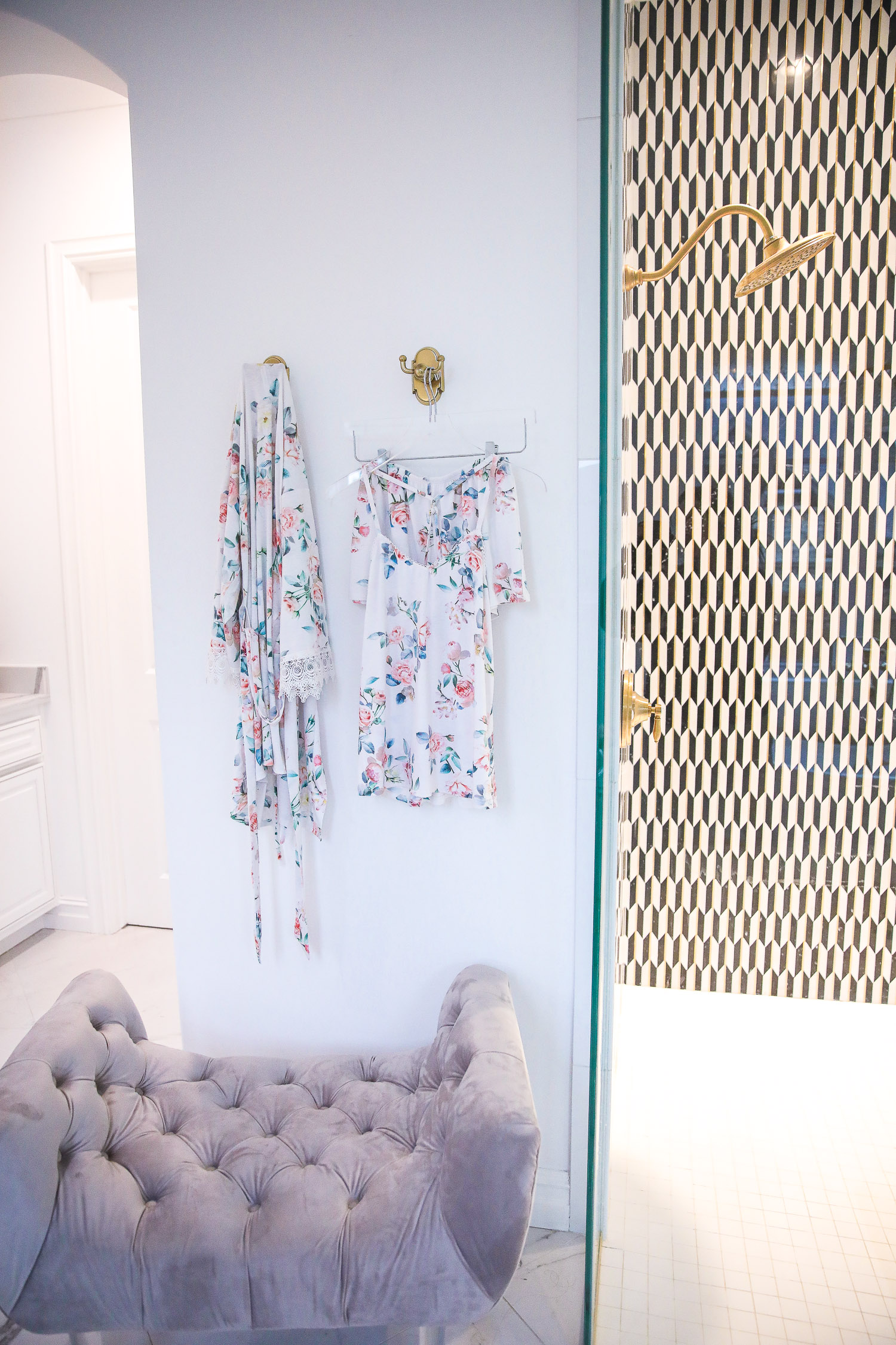 flora nikrooz pajamas and robe, Emily Gemma, | Nighttime Routine by popular US beauty blog, The Sweetest Thing: image of a bathroom with a grey velvet tuft bench, walk in shower with black and white tiles and a gold shower head, and a floral print wrap and floral print short pajama set hanging on gold wall hooks.