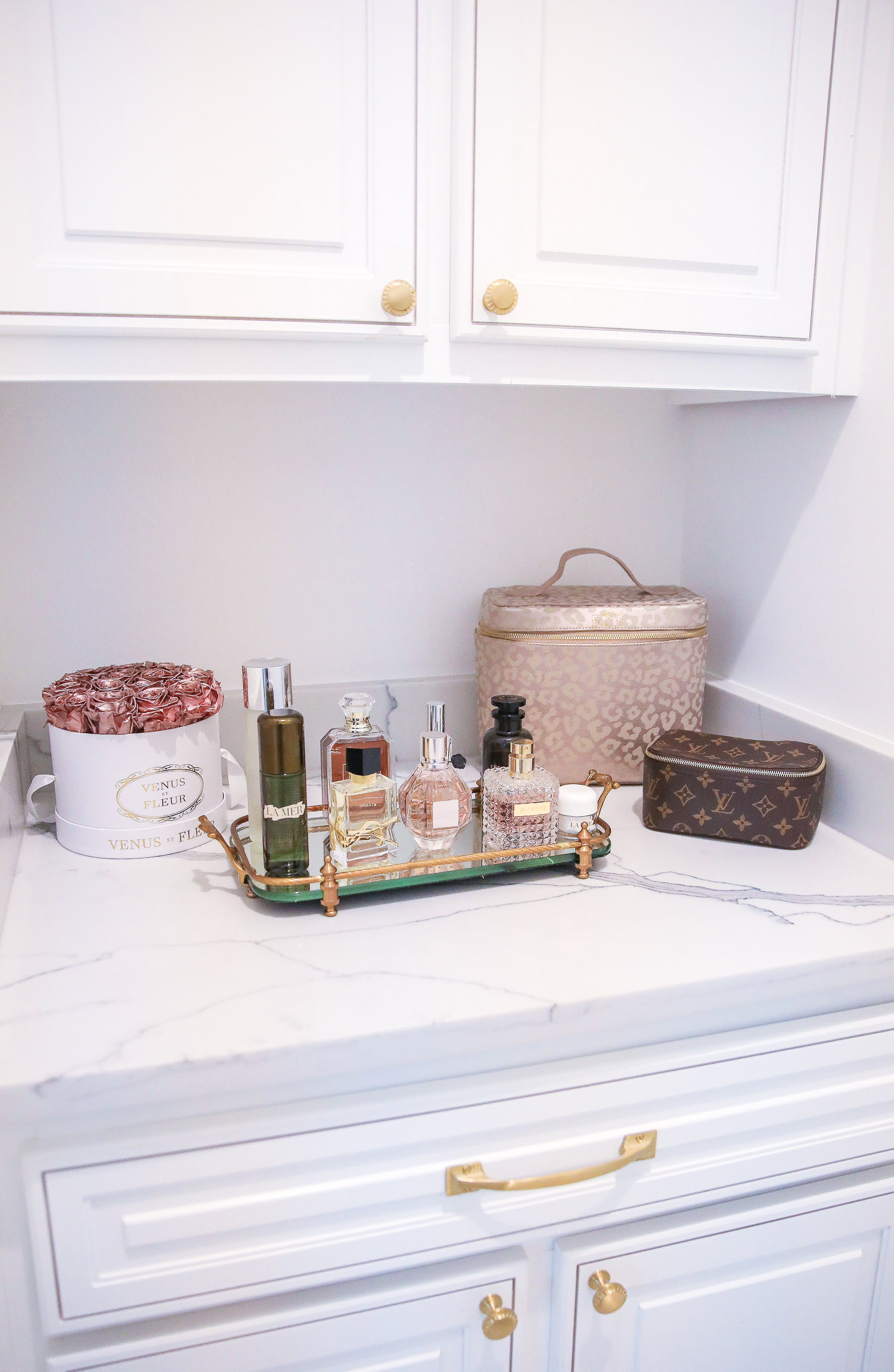 perfume tray, master bathroom decor, Louis Vuitton perfume | Nighttime Routine by popular US beauty blog, The Sweetest Thing: image of a bathroom with a gold tray containing various perfumes, Louis Vuitton makeup case, and leopard print makeup case.