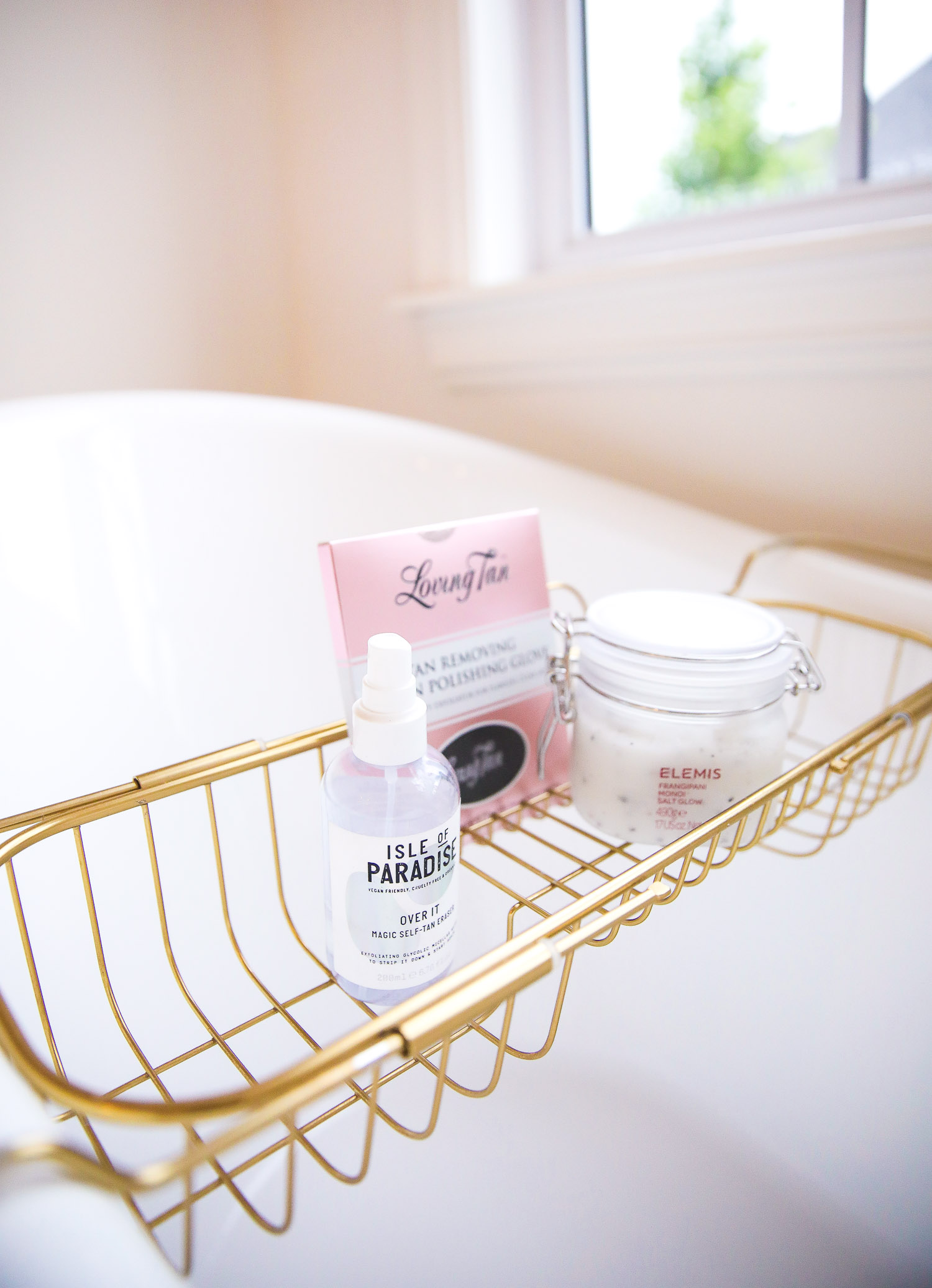 loving tan 2 hour express review, best self tanner, best self tanner remover, isle of paradise self tanner remover, Emily Gemma | Nighttime Routine by popular US beauty blog, The Sweetest Thing: image of white claw foot bathtub with a gold tub rack containing a bottle of isle of Paradise, Loving Tan, and Elemis salt glow.