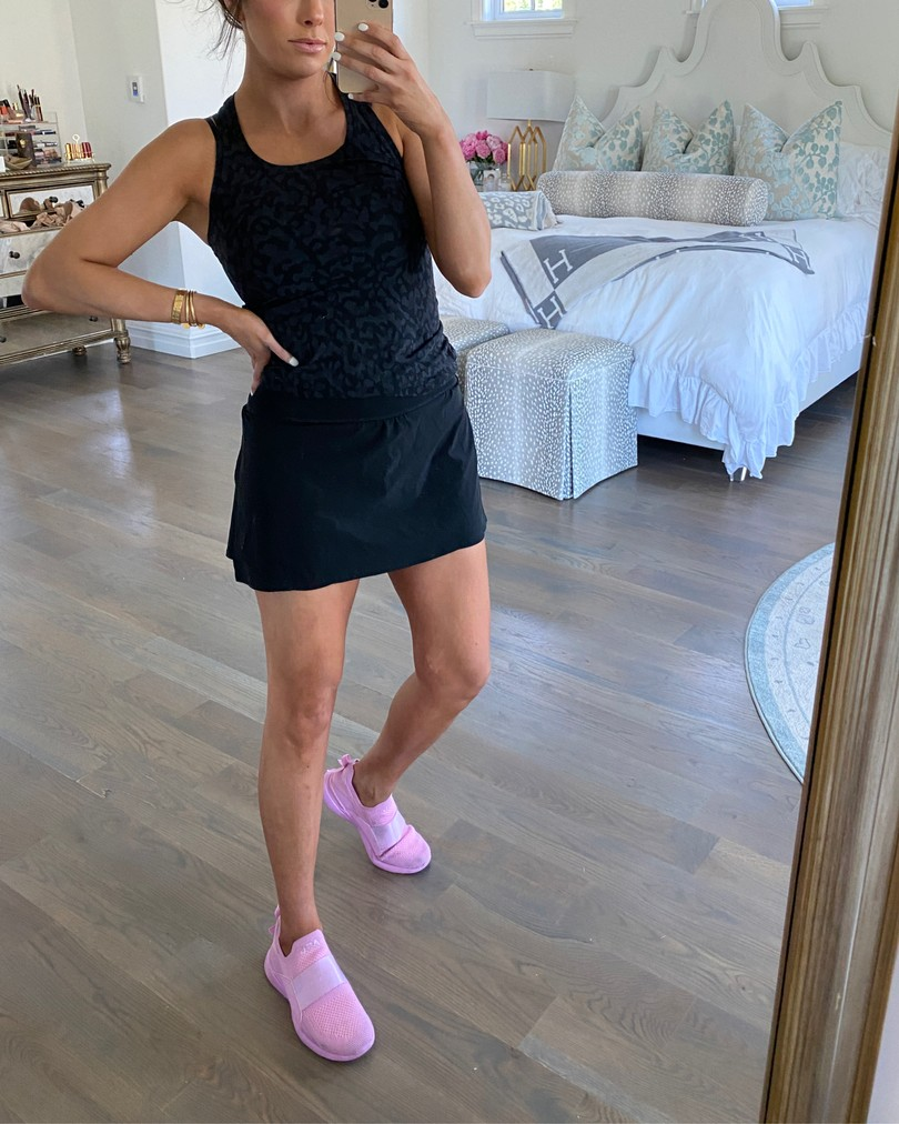 Cute Workout Clothes by popular US fashion blog, The Sweetest Thing: image of Emily Gemma standing in her bedroom and wearing a Spanx skort, Lululemon tank, APL sneakers, and a Lululemon sports bra.