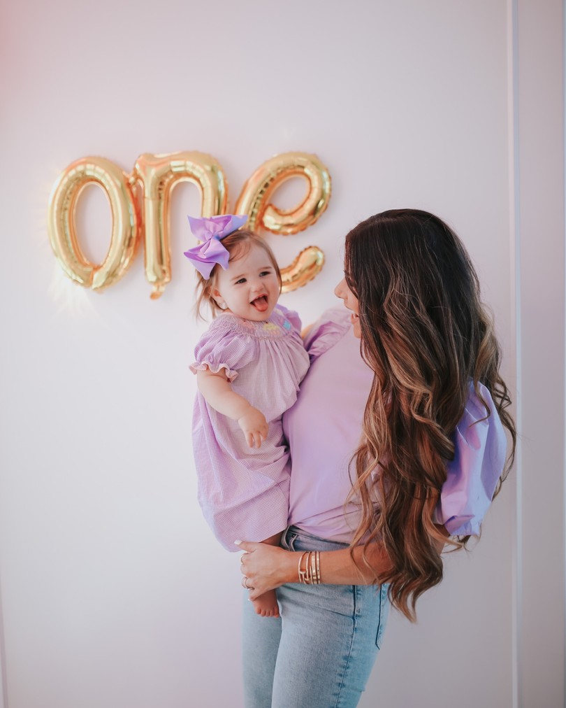 Instagram Recap by popular US life and style blog, The Sweetest Thing: image of Emily Gemma holding her daughter Sophie on her hip in front of a gold 'One' sign and wearing Mother denim, H&M Puff-sleeved Top, and Smocked Auctions SWEET CUPCAKES SMOCKED BISHOP LAVENDER GINGHAM.