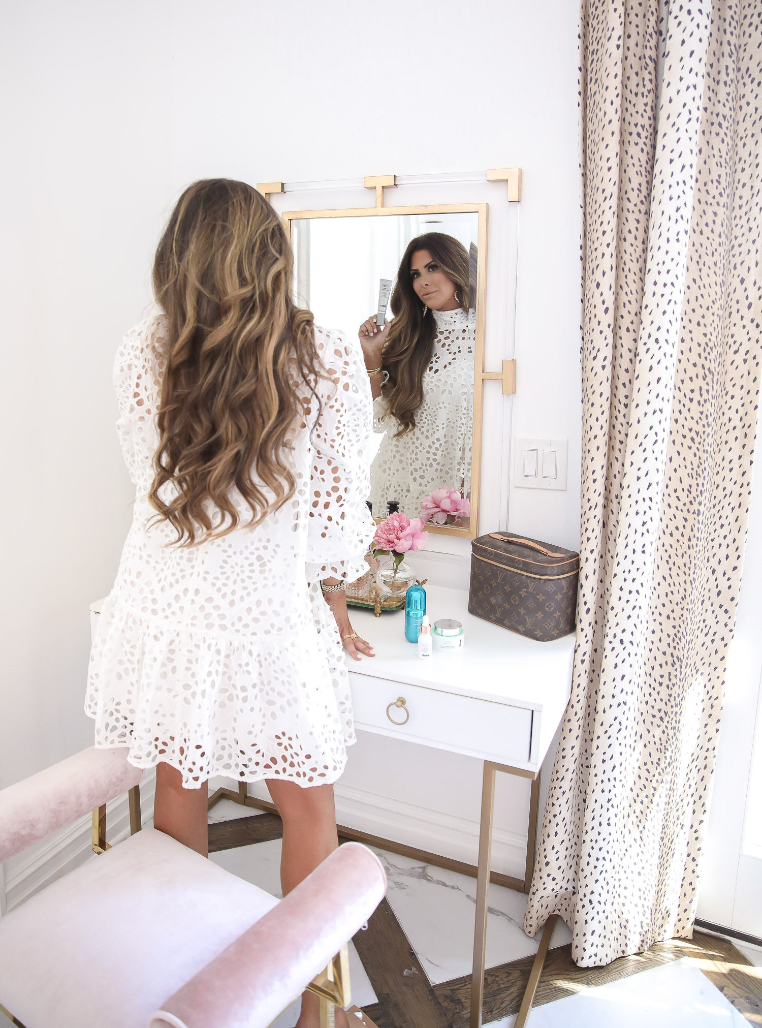 Dr Brandt Pore Refiner Primer by popular US beauty blog, The Sweetest Thing: image of Emily Gemma wearing a H & M Eyelet Embroidery Dress and holding a bottle of Dr Brandt Pore Refiner Primer while standing at her vanity.