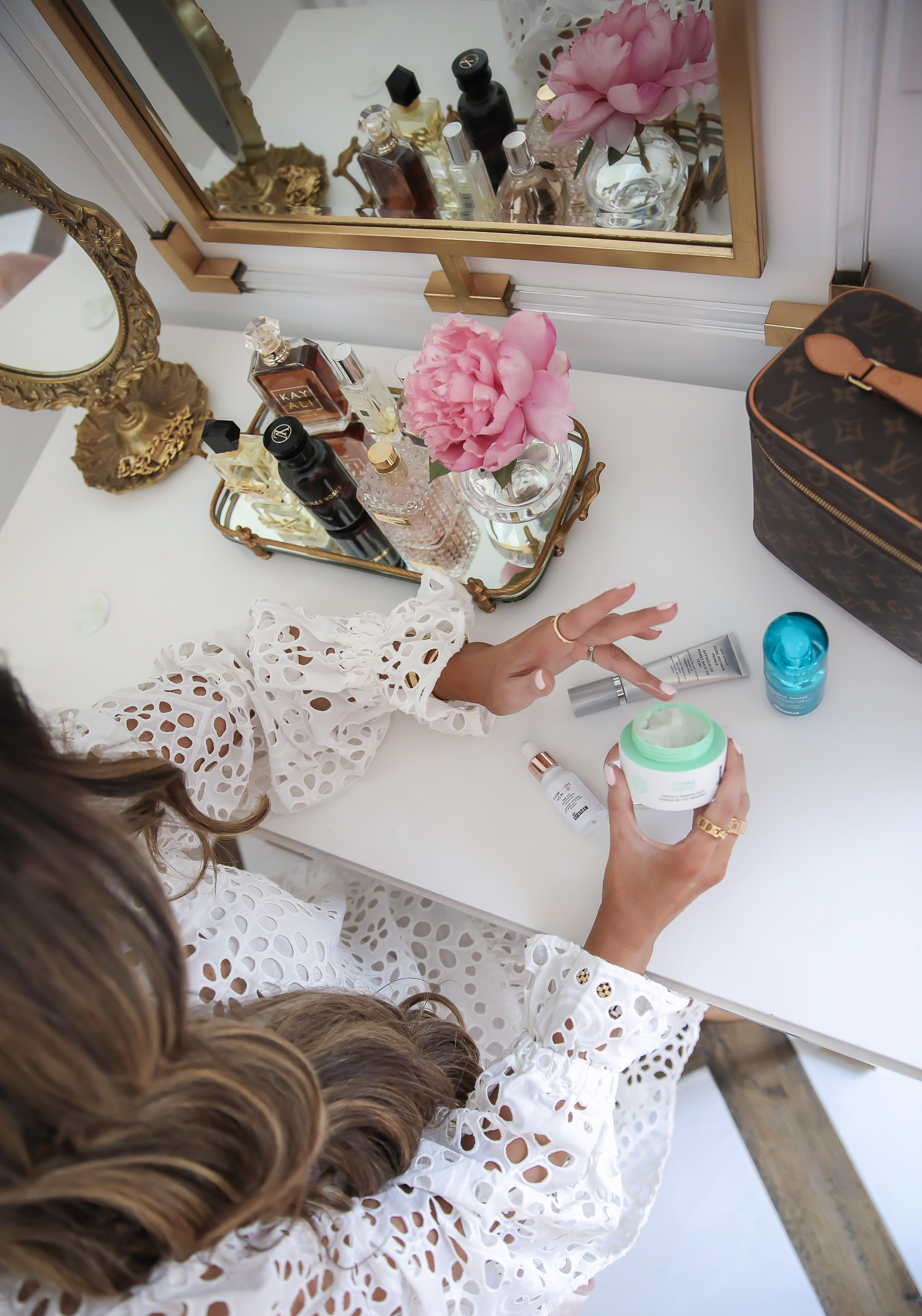 Dr Brandt Pore Refiner Primer by popular US beauty blog, The Sweetest Thing: image of Emily Gemma wearing a H & M Eyelet Embroidery Dress and holding a bottle of Dr Brandt Hydro Biotic while sitting at her vanity.