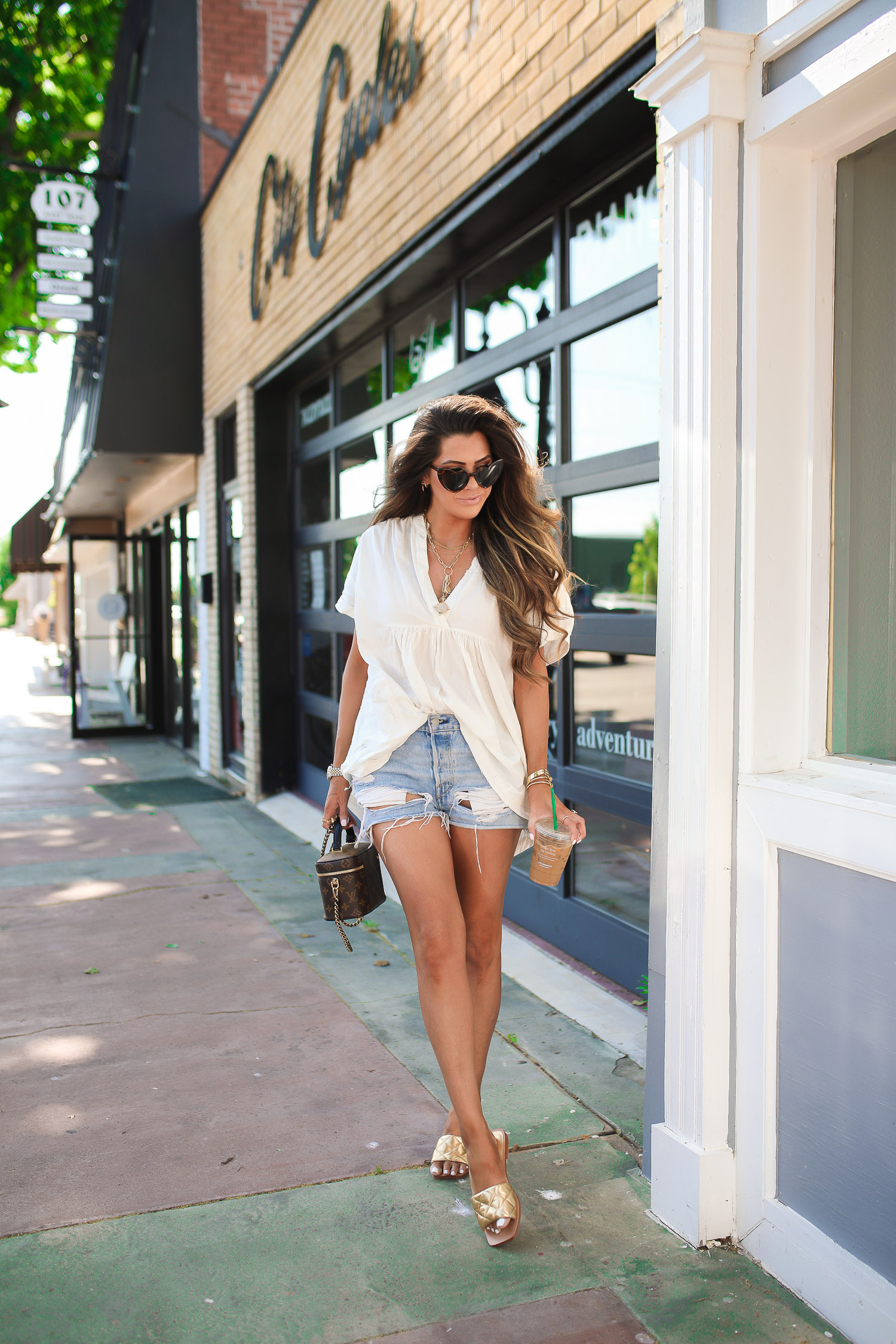 summer fashion pinterest 2020, emily gemma, bottaga venetta sandal dupes, Free people oversized white tunic, Levis 501 shorts review, YSL heart sunglasses-11 | Free People Tunic Top by popular US fashion blog, The Sweetest Thing: image of Emily Gemma walking outside and wearing a Nordstrom Getaway with Me Tunic Top, Nordstrom 501® Original Cutoff Denim Shorts LEVI'S®, Nordstrom Reta Slide Sandal MARC FISHER LTD, Nordstrom Loulou 54mm Heart Sunglasses SAINT LAURENT, Nordstrom Pavé Huggie Hoop Earrings NORDSTROM, Rolex watch, Cartier bracelets, Nordstrom Lip Cheat Lip Liner CHARLOTTE TILBURY, Nordstrom Hot Lips Lipstick CHARLOTTE TILBURY, and Nordstrom Gloss Luxe Moisturizing Lipgloss TOM FORD while holding a Starbuck's drink and Louis Vuitton purse.