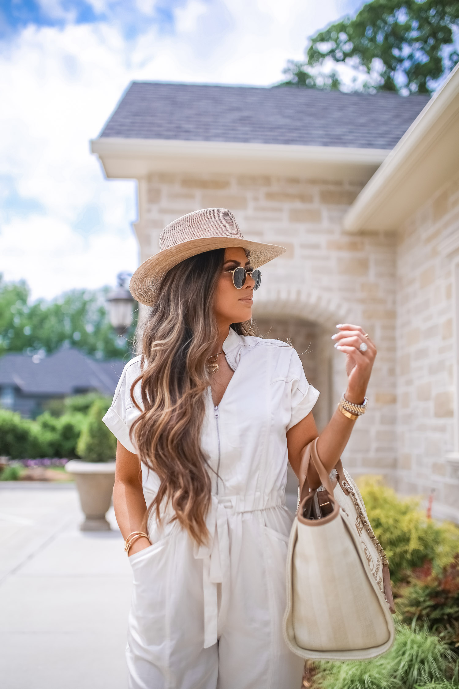Off White Jumpsuit by popular US fashion blog, The Sweetest Thing: image of a woman wearing a Express Zip Front Utility Jumpsuit, Nordstrom heeled sandals, Express Large Metal Hoop Earrings, Cartier jewelry, a straw hat, and holding a Chanel bag.