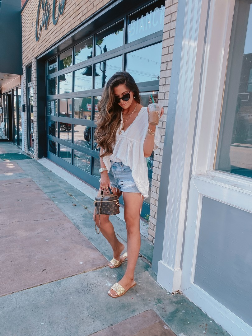 Instagram Recap by popular US life and style blog, The Sweetest Thing: image of Emily Gemma wearing a Free People tunic top, Levi's shorts, gold slide sandals, cartier bracelets, Cartier rings, Fendi Rings, Dior rings, Nordstrom Pave huggie earrings, and holding a Louis Vuitton bag.