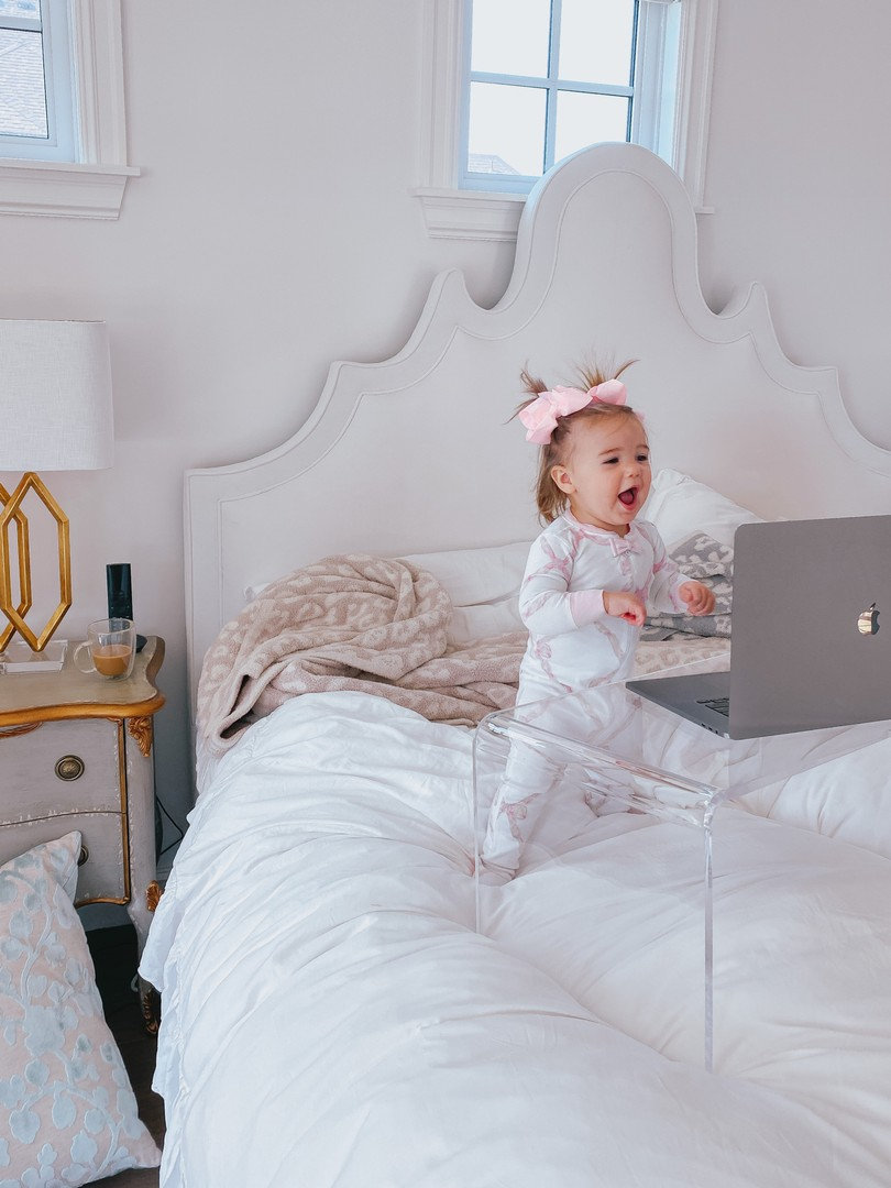 Instagram Recap by popular US life an style blog, The Sweetest Thing: image of a baby girl wearing a pair of Beaufort Bonnet pajamas and standing in front of a Lavish Home acrylic table with a open laptop on it on a bed with a white headboard and white comforter.