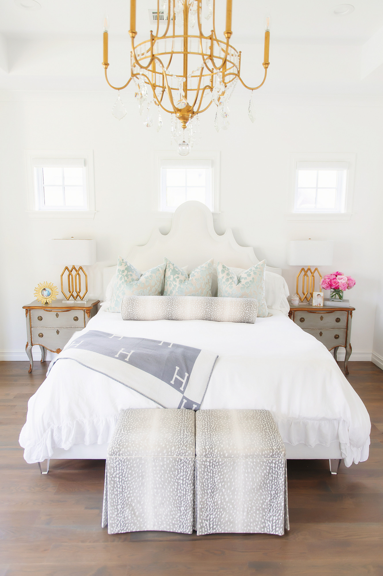 Blog Design by popular US lifestyle blog, The Sweetest Thing: image of Emily Gemma's master bedroom with a gold and crystal chandelier, grey wood night stands, antelope print bench, and a bed with a fabric headboard, antelope print lumbar pillow and white duvet cover.