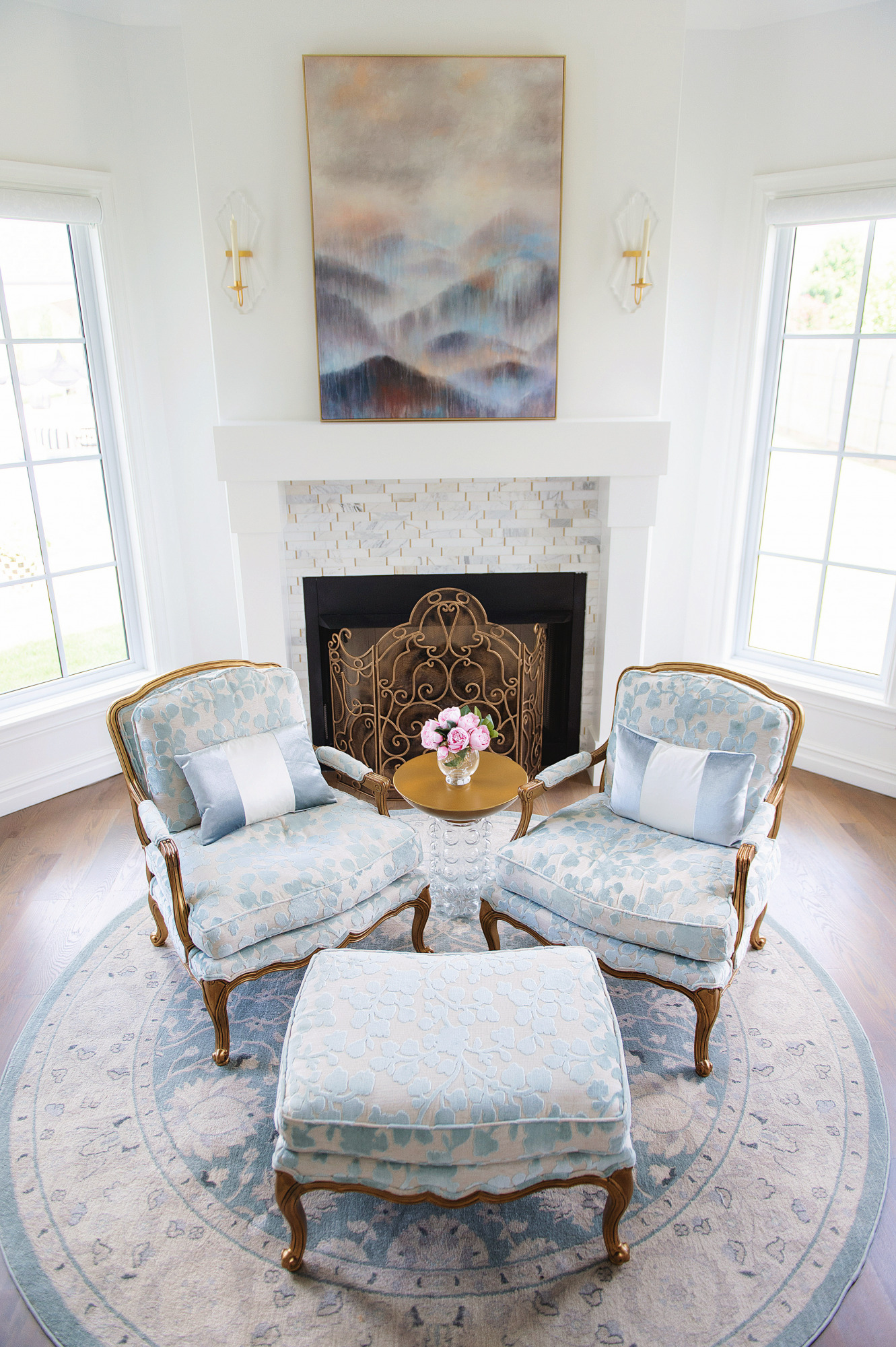 Blog Design by popular US lifestyle blog, The Sweetest Thing: image of a sitting nook with a blue and white print round rug, matching blue and cream arm chairs, and a fireplace with a gold grate.