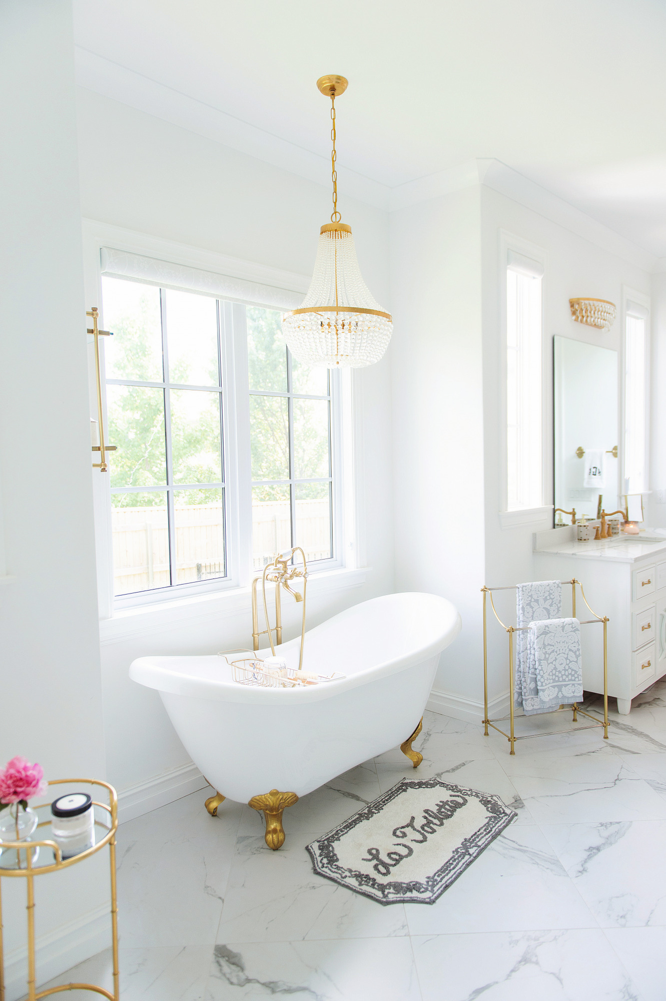 Blog Design by popular US lifestyle blog, The Sweetest Thing: image of a bathroom with a white and gold claw foot tub, chandelier, and white vanity.