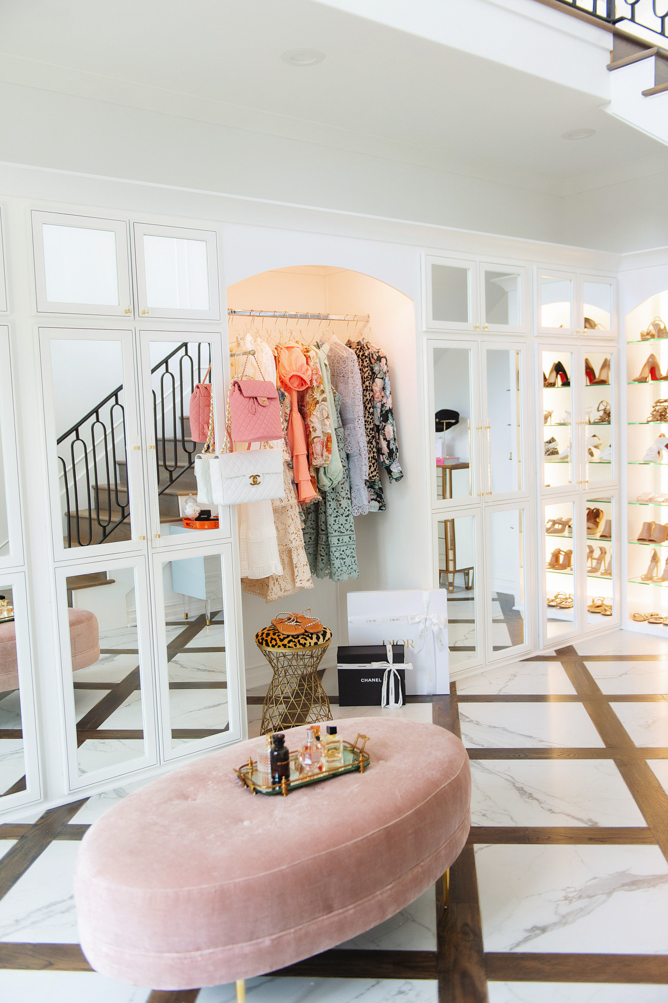 Blog Design by popular US lifestyle blog, The Sweetest Thing: image of a two story closet filled with a tufted pink velvet bench, shoe display and clothing rack filled with designer dresses.
