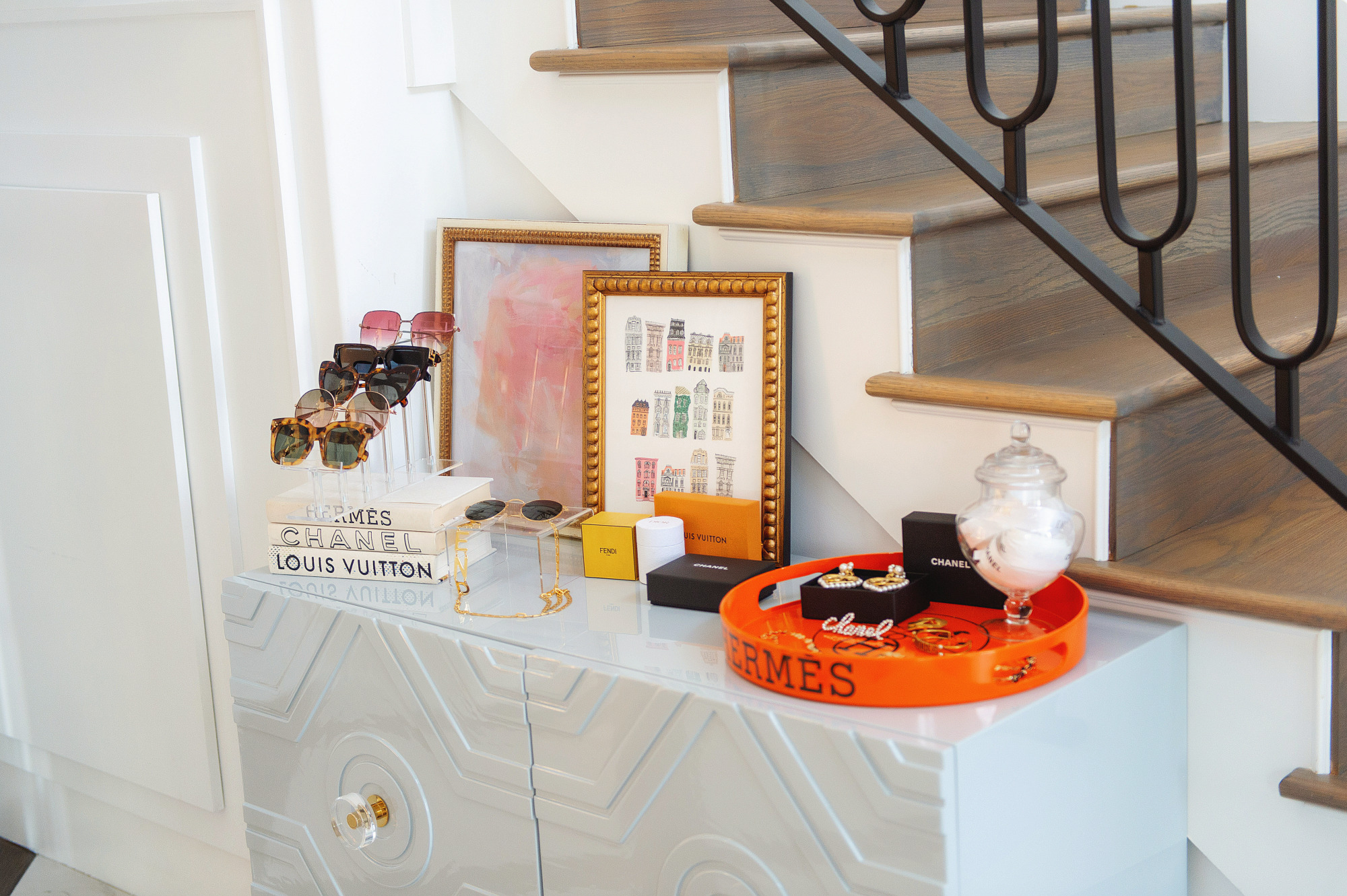 Blog Design by popular US lifestyle blog, The Sweetest Thing: image of a grey enamel dresser with an acrylic sunglasses display, Hermes tray, artwork in gold frames, and Chanel jewelry.