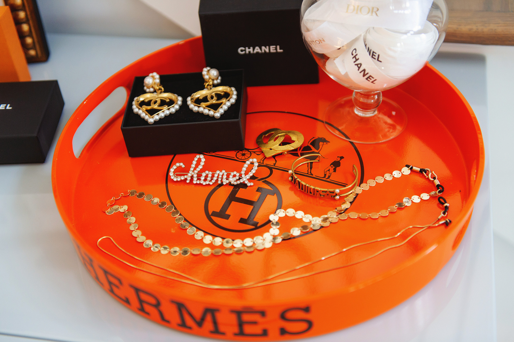 Blog Design by popular US lifestyle blog, The Sweetest Thing: image of a Hermes tray containing Chanel earrings, a Chanel hair clip, and some gold necklaces.