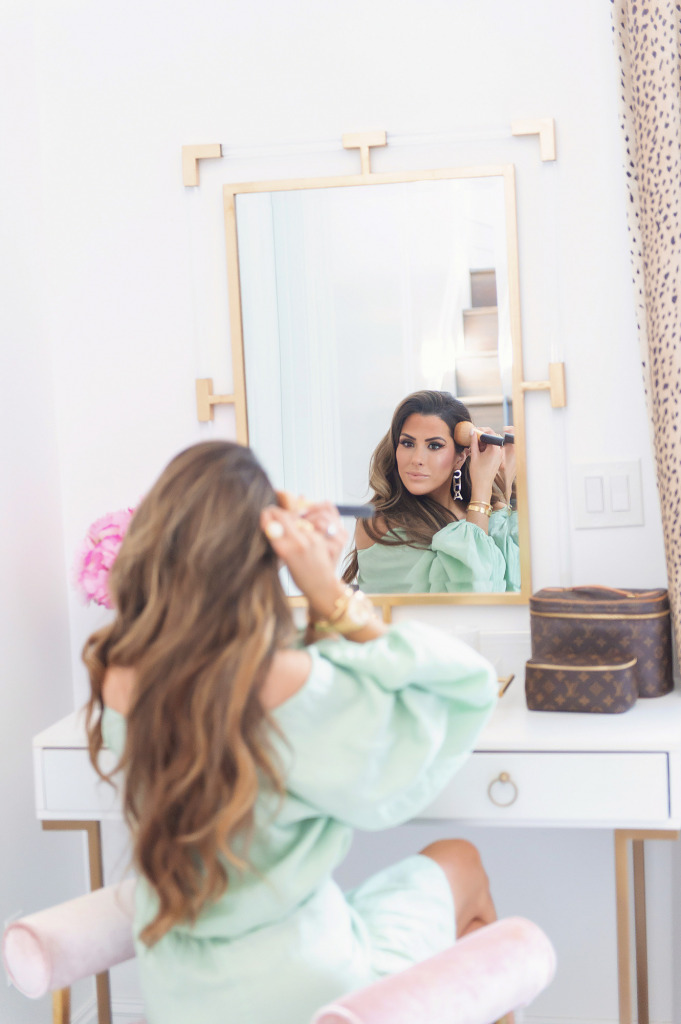Blog Design by popular US lifestyle blog, The Sweetest Thing: image of Emily Gemma wearing a mint green dress and sitting on a pink velvet bench while she sits at her vanity and applies her makeup.
