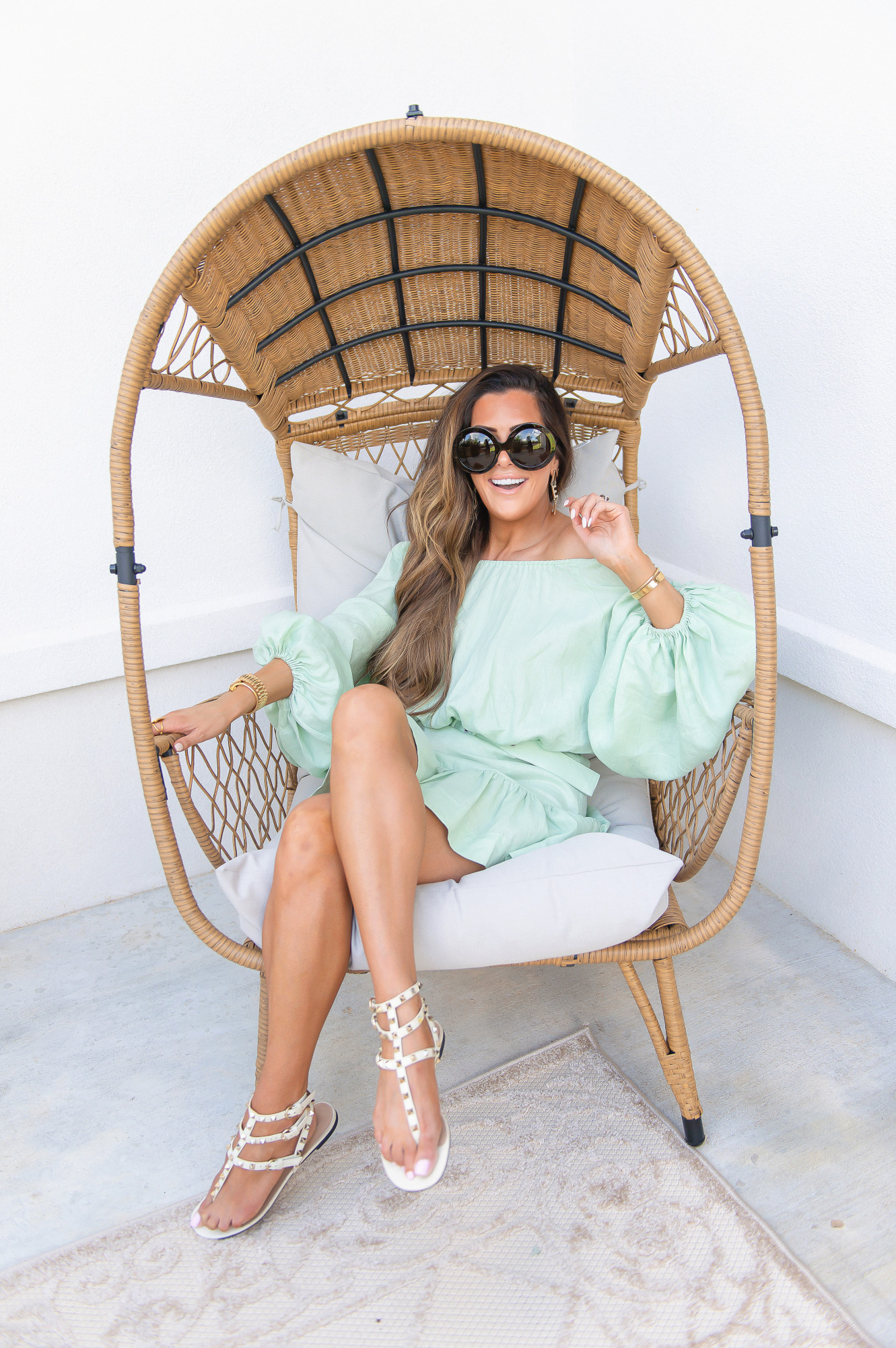 Blog Design by popular US lifestyle blog, The Sweetest Thing: image of Emily Gemma wearing a mint green dress and sitting in a rattan egg chair.