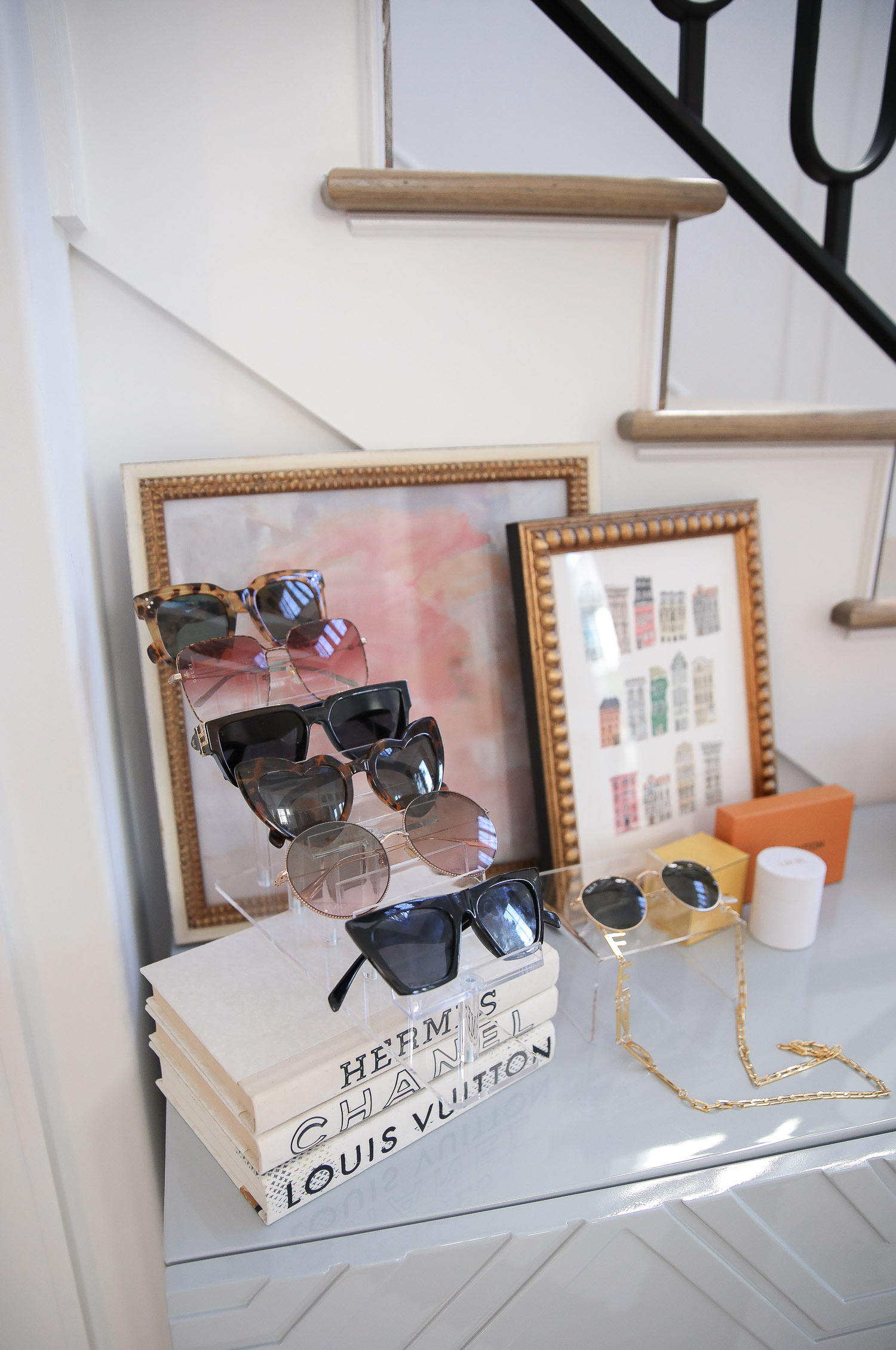 amazon must haves summer 2020, amazon home decor blog post, amazon luxury must haves, two story closet pinterest, emily gemma, closet organization | Amazon Favorites by popular US life and style blog, The Sweetest Thing: image of Urban Outfitter sunglasses, YSL sunglasses, Louis Vuitton sunglasses, and Dior sunglasses, organized on an acrylic display riser that's resting on top of a stack of Nordstrom Designer Reclaimed Book Art E. LAWRENCE, LTD. that's next to an Hermes tray and framed Parisian living wall art.