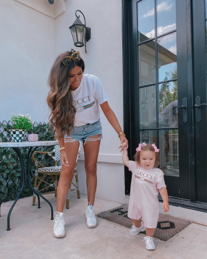 Instagram Recap by popular US life an style blog, The Sweetest Thing: image of Emily Gemma standing outside with her daughter Sophie and wearing a Gucci t-shirt, Gucci onesie, cutoff denim shorts, Reebok shoes, and Urban Outfitters sunglasses.