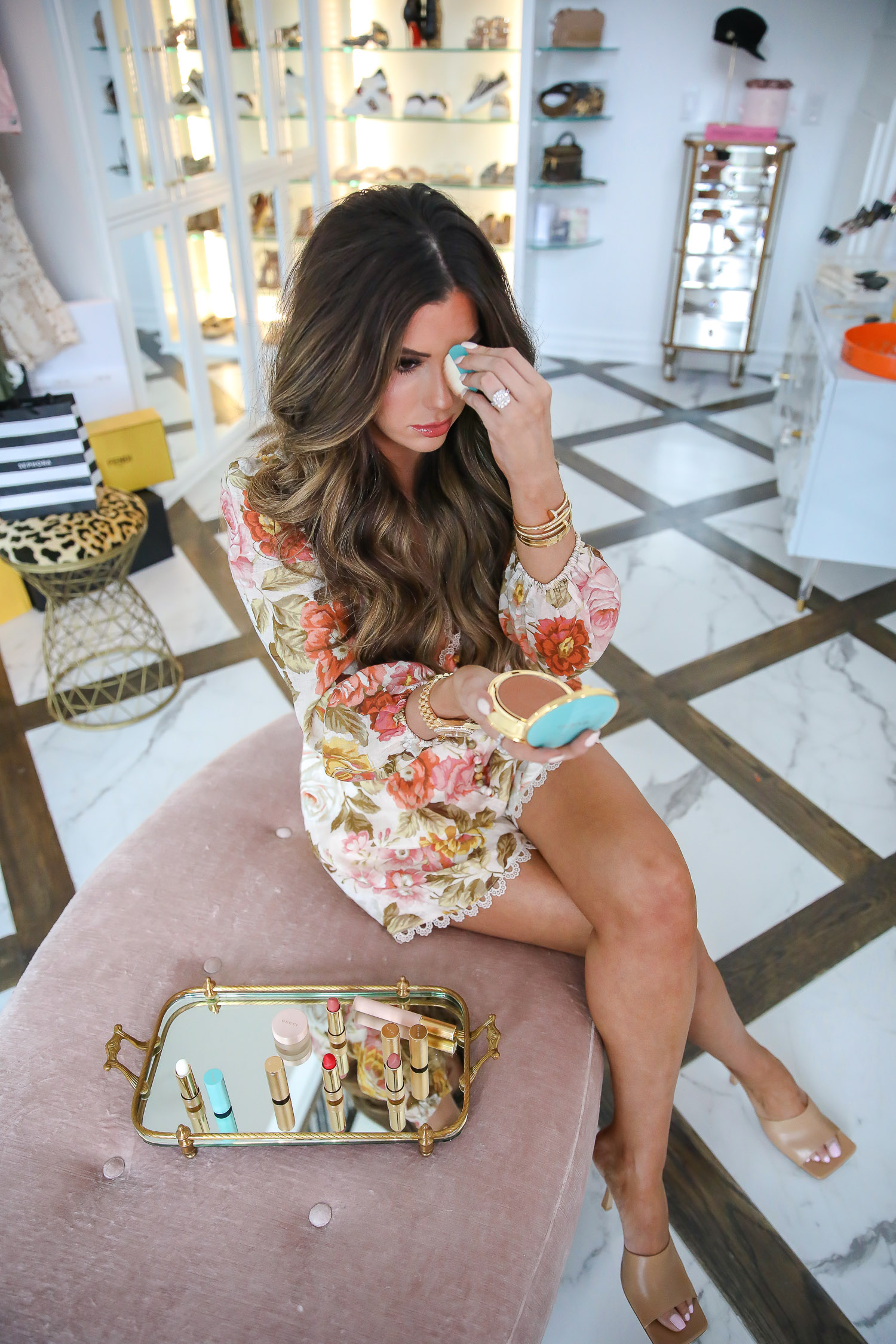 Gucci bronzer review by popular US beauty blog, The Sweetest Thing: image of Emily Gemma wearing a floral romper and sitting on a tuft velvet ottoman while applying Gucci Poudre De Beauté Éclat Soleil Bronzing Powder.
