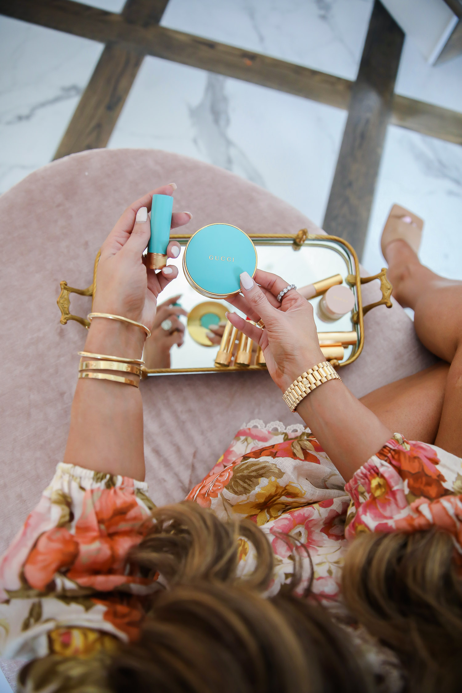 Gucci bronzer review by popular US beauty blog, The Sweetest Thing: image of Emily Gemma wearing a floral romper and sitting on a tuft velvet ottoman while holding some Gucci Poudre De Beauté Éclat Soleil Bronzing Powder and Gucci lipstick.