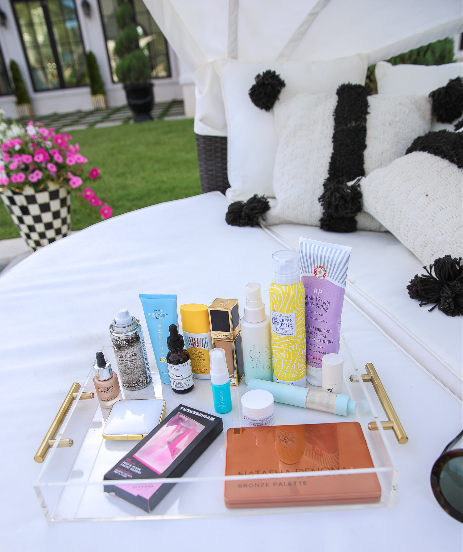 sephora haul beauty blogger july 2020, natasha denona bronze palette review, best dry shampoo at sephora, tarte SPF powder, emily gemma house | Sephora Favorites by popular US beauty blog, The Sweetest Thing: image of an acrylic tray filled with Sephora natasha denona bronze palette, tarte SPF powder, URBAN DECAY Naked Ultraviolet Eyeshadow Palette, SUPERGOOP! PLAY Body Mousse SPF 50 with Blue Sea Kale, COOLA Makeup Setting Spray Organic Sunscreen SPF 30, FIRST AID BEAUTY KP Bump Eraser Body Scrub with 10% AHA, TOM FORD Traceless Soft Matte Foundation, ICONIC LONDON Illuminator Liquid Highlight, FIRST AID BEAUTY Eye Duty Niacinamide Brightening Eye Cream, TWEEZERMAN Prep & Plane Facial Razors, IGK First Class Charcoal Detox Dry Shampoo, DOMINIQUE COSMETICS Ultra Hydrating Fine Mist, The Ordinary Caffeine Solution 5% + EGCG, and TOM FORD Highlighting Duo.