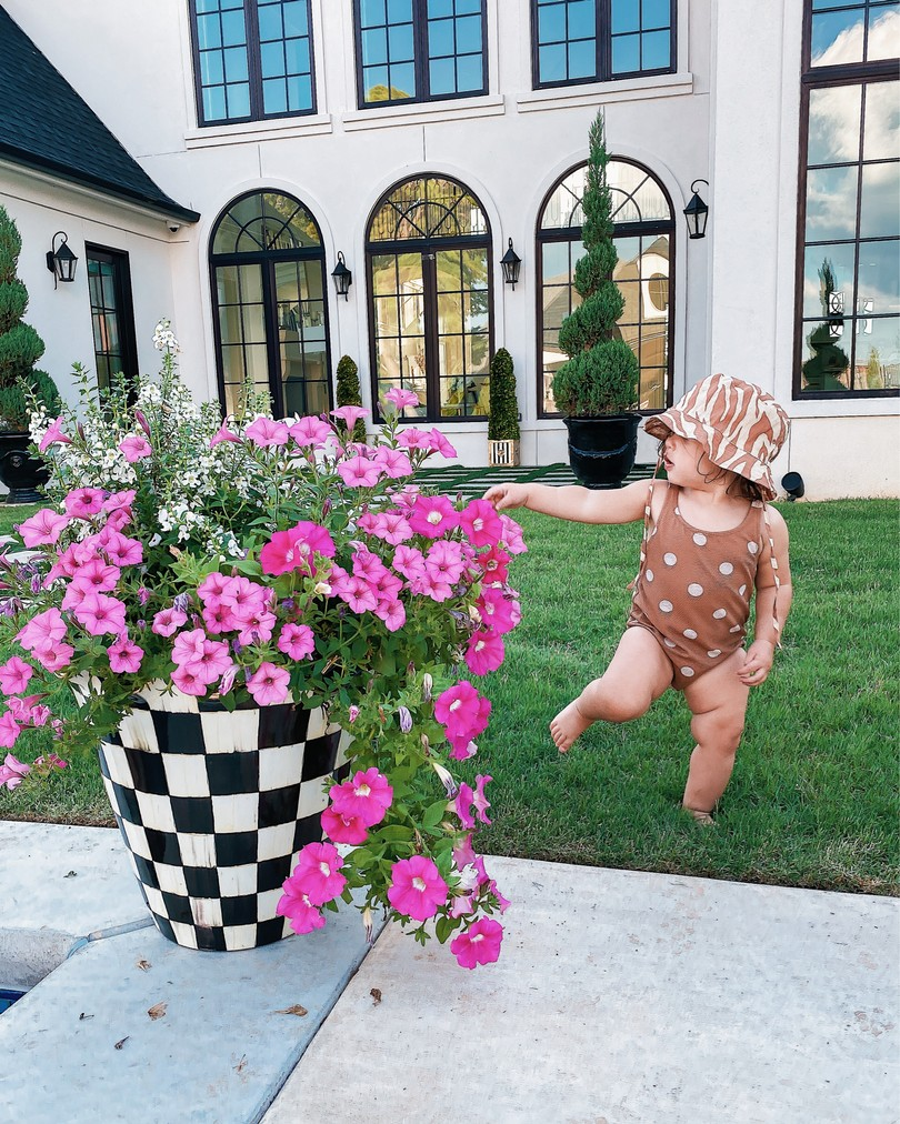 backyard decor, Mackenzie-Childs, Baby swimsuits, Emily Ann Gemma  Instagram Recap by popular US life and style blog, The Sweetest Thing: image of a baby girl standing next to a Mackenzie-Childs flower pot and wearing a H&M hat and H&m brown and white polka dot swimsuit.
