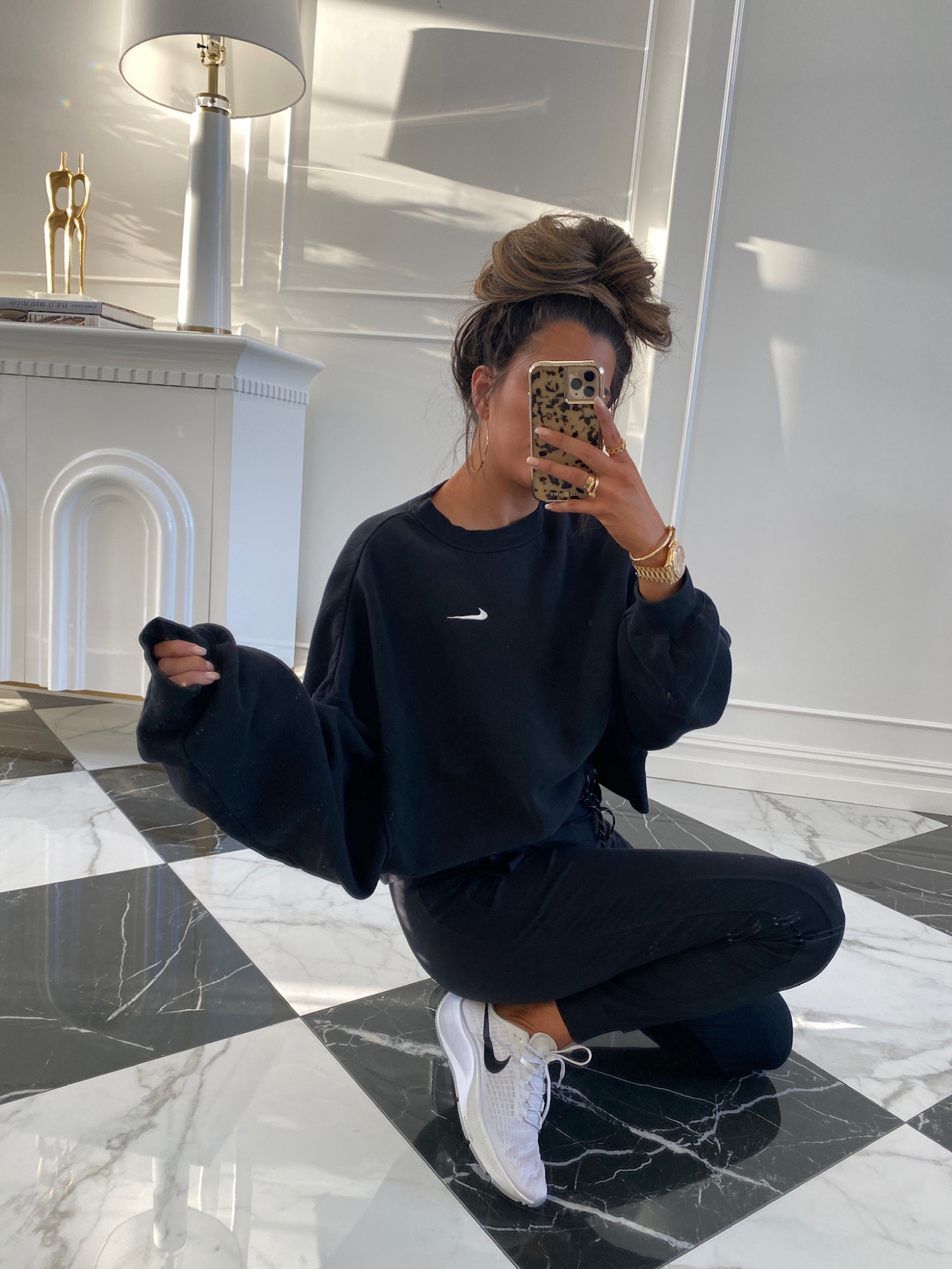 Nordstrom Anniversary Sale 2021 favorites by top US fashion blogger, The Sweetest Thing. | Nordstrom Anniversary Sale by popular US fashion blog, The Sweetest Thing: image of Emily Gemma wearing a black Nike sweatshirt, black joggers, and grey Nike sneakers.