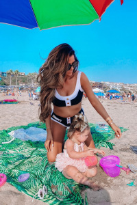 summer fashion 2020, swimsuit outfits, beach outfits, Emily Ann Gemma  Instagram Recap by popular US life and style blog, The Sweetest Thing: image of Emily Gemma sitting on the sand with her daughter while at the beach and wearing a black an white bikini.