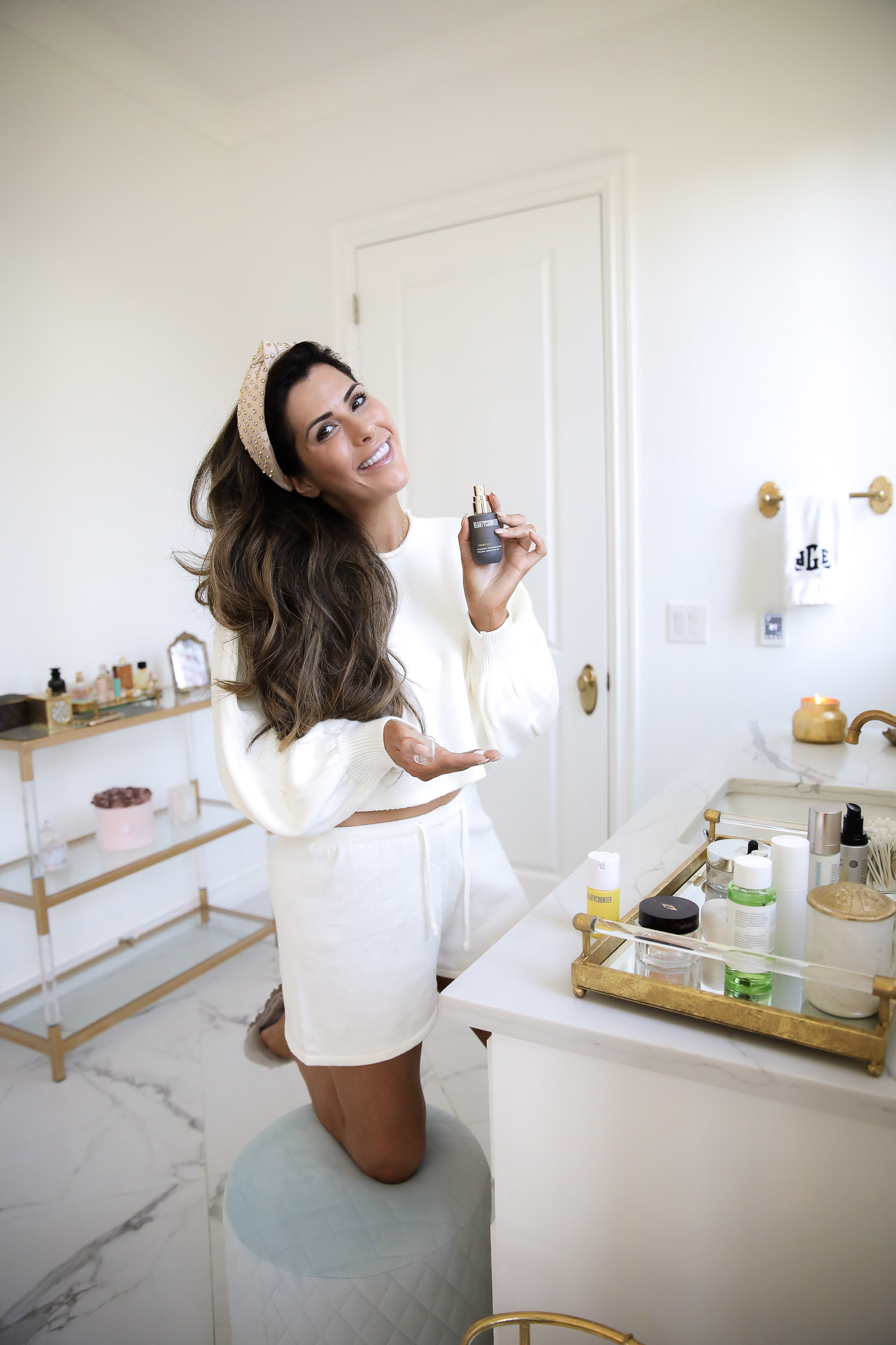 beauty counter review vitamin C, Beauty Counter Sephora overnight resurfacing gel, emily ann gemma |  Beautycounter Products by popular US beauty blog, The Sweetest Thing: image of Emily Gemma wearing a cream sweater set and holding up a bottle of Beautycounter Counter+ Overnight Resurfacing Peel.