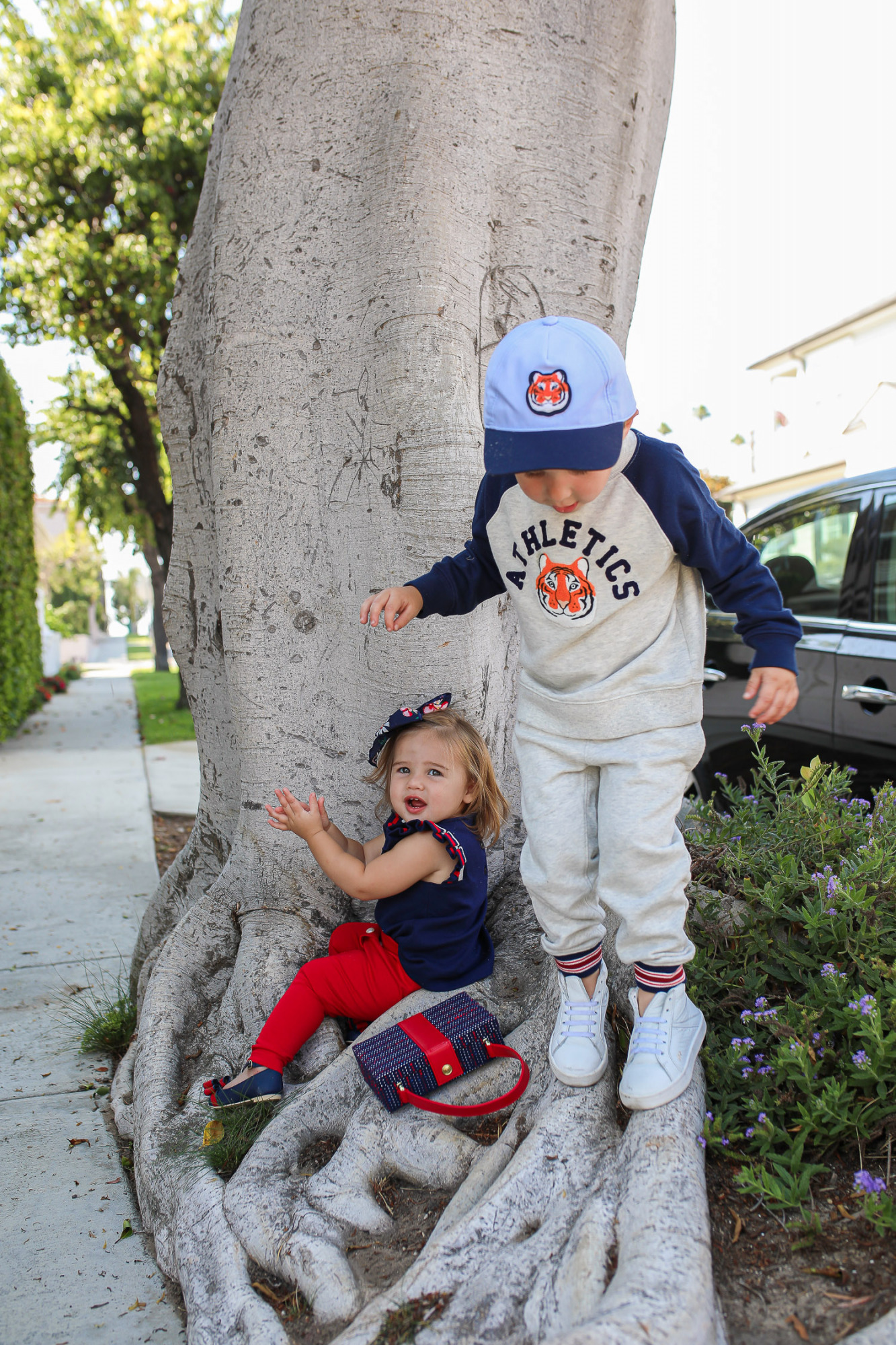 Janie and Jack by popular US fashion Blog, The Sweetest Thing: image of two kids walking outside on a sidewalk in Newport Beach, CA and wearing a Janie and Jack TIGER PATCH CAP, Janie and Jack RAGLAN TIGER SWEATSHIRT, Janie and Jack STRIPE TRIM JOGGER, Janie and Jack PLEATED SLEEVE TOP, Janie and Jack BUTTON PONTE PANT, Janie and Jack BOW ANKLE STRAP FLAT, FLORAL BOW BARRETTE, and Janie and Jack BOUCLÉ PURSE.
