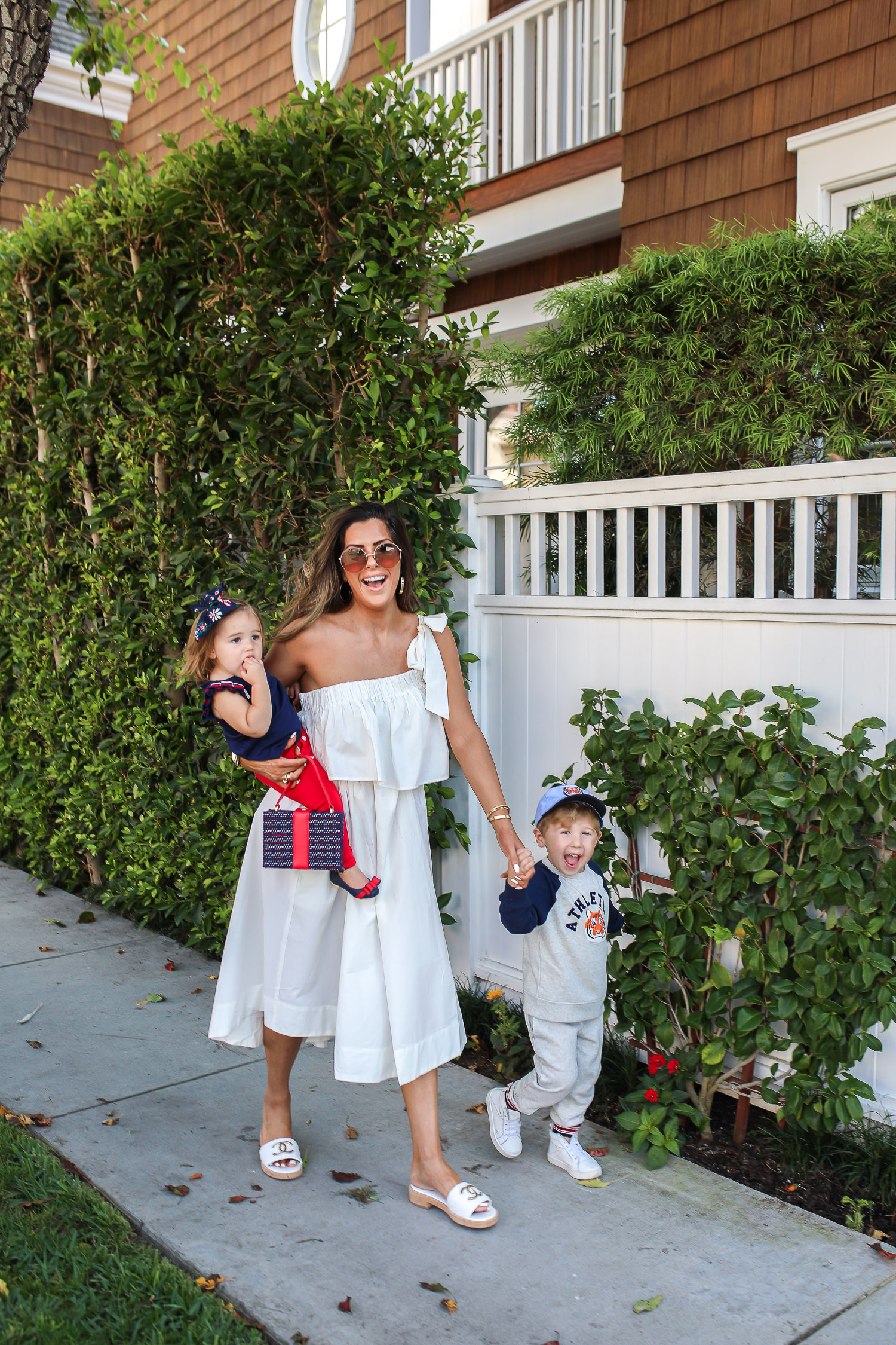 Janie and Jack by popular US fashion Blog, The Sweetest Thing: image of a mom and her two kids walking outside on a sidewalk in Newport Beach, CA and wearing a white one shoulder dress and white Channel slide sandals, Janie and Jack TIGER PATCH CAP, Janie and Jack RAGLAN TIGER SWEATSHIRT, Janie and Jack STRIPE TRIM JOGGER, Janie and Jack PLEATED SLEEVE TOP, Janie and Jack BUTTON PONTE PANT, Janie and Jack BOW ANKLE STRAP FLAT, FLORAL BOW BARRETTE, and Janie and Jack BOUCLÉ PURSE.
