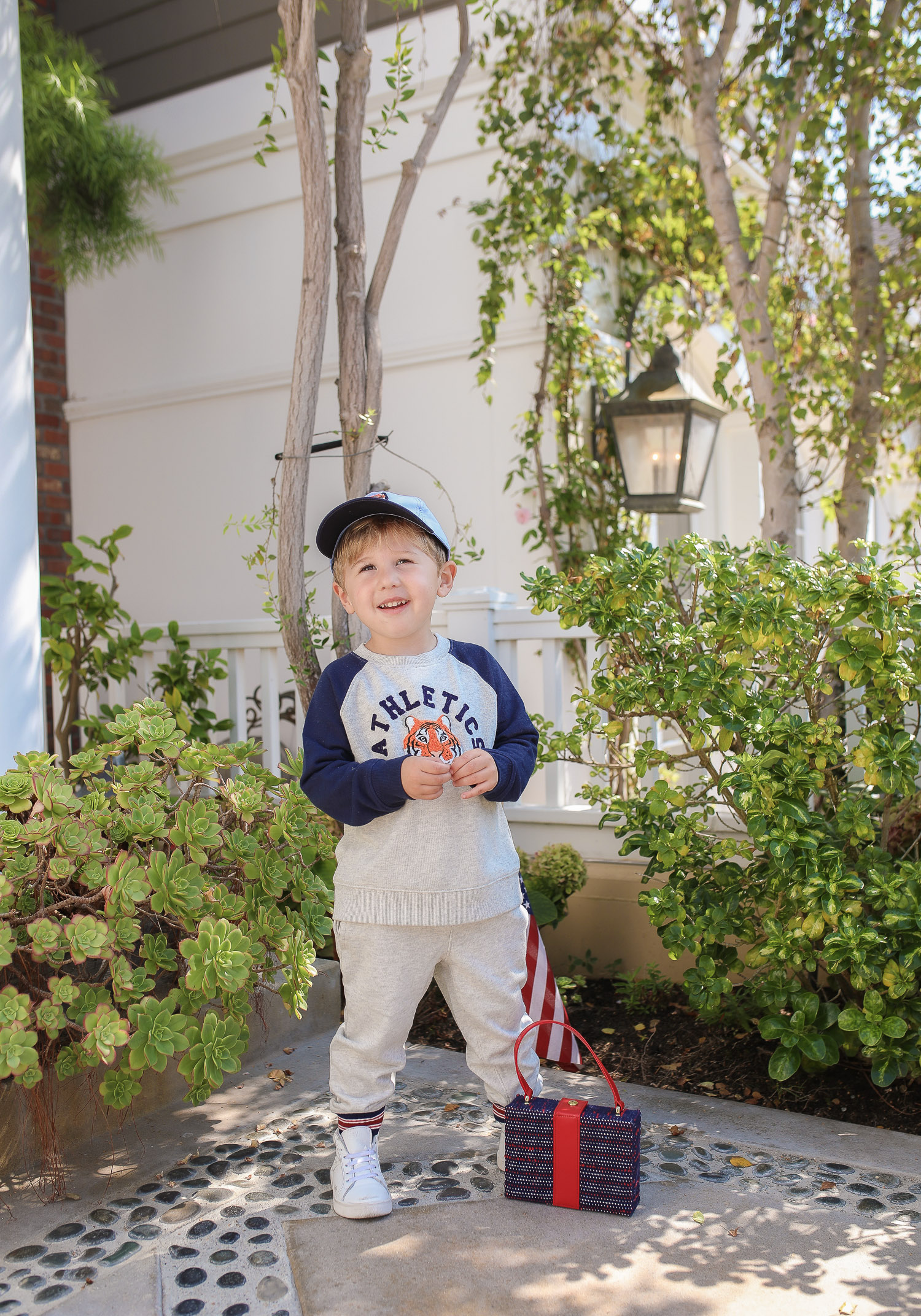 Janie and Jack by popular US fashion Blog, The Sweetest Thing: image of a young boy sitting outside on the ground in Newport Beach, CA and wearing a Janie and Jack TIGER PATCH CAP, Janie and Jack RAGLAN TIGER SWEATSHIRT, Janie and Jack STRIPE TRIM JOGGER.
