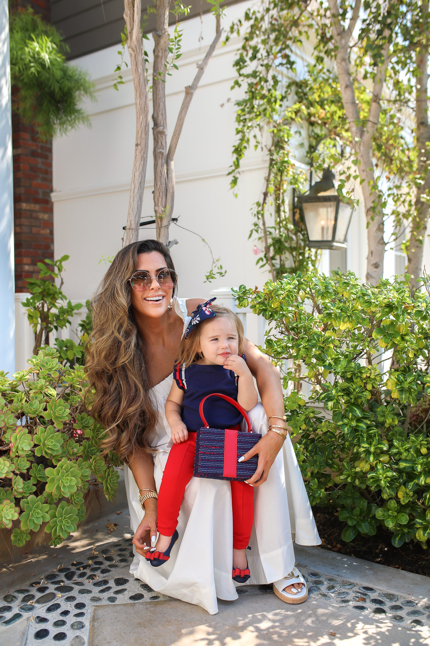 Janie and Jack by popular US fashion Blog, The Sweetest Thing: image of a mom holding her daughter outside in Newport Beach, CA and wearing a white one shoulder dress and white Channel slide sandals and Janie and Jack PLEATED SLEEVE TOP, Janie and Jack BUTTON PONTE PANT, Janie and Jack BOW ANKLE STRAP FLAT, FLORAL BOW BARRETTE, and Janie and Jack BOUCLÉ PURSE.
