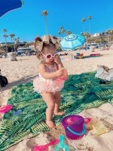 summer fashion 2020, swimsuit outfits, beach outfits, Emily Ann Gemma, Baby swimsuits  Instagram Recap by popular US life and style blog, The Sweetest Thing: image of a baby girl standing in the sand at the beach and wearing daisy frame sunglasses and a Maisonette swimsuit.