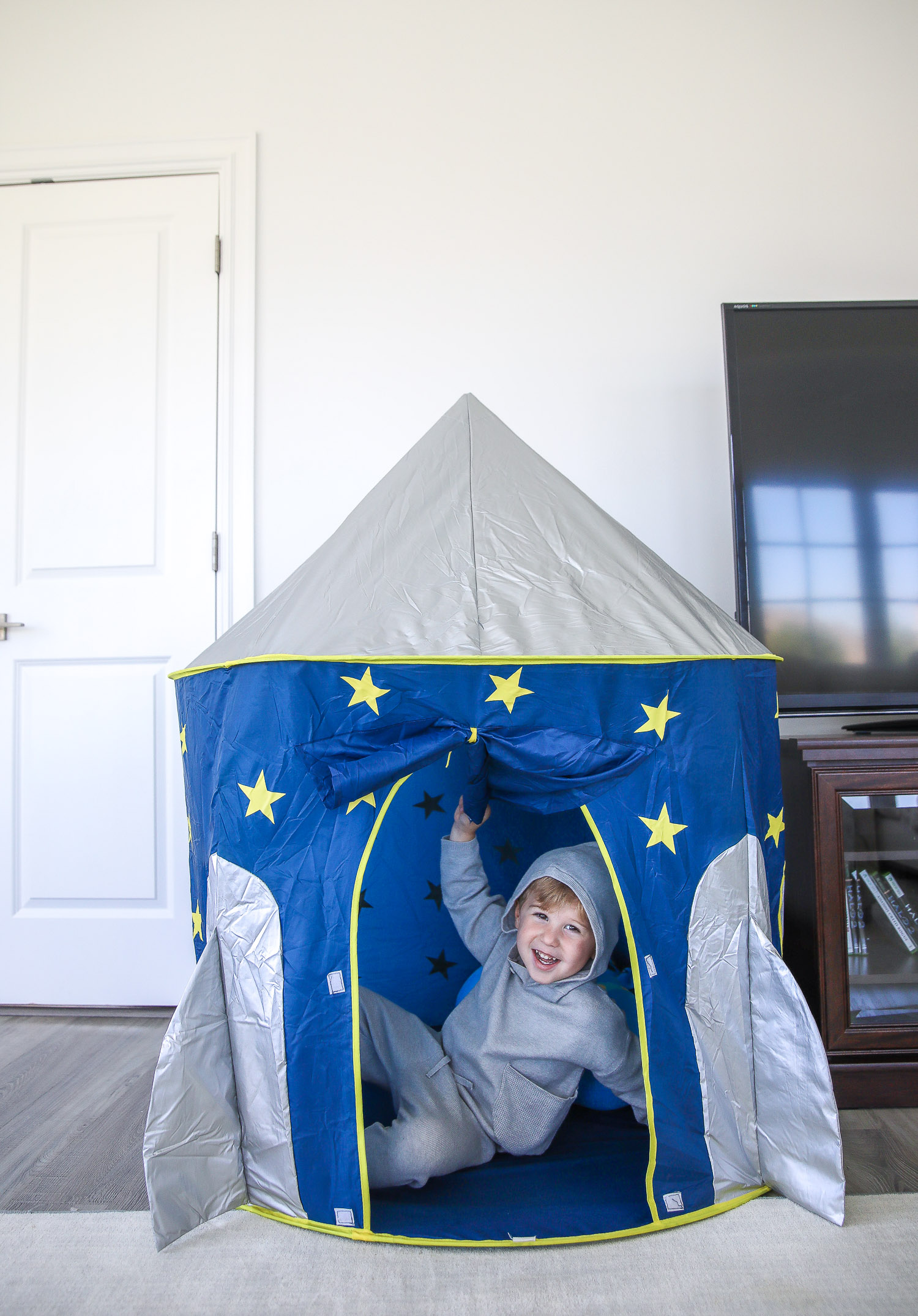 walmart kids home organization must haves, playroom organization ideas, emily gemma, the sweetest thing blog | Playroom Organization by popular US life and style blog, The Sweetest Thing: image of a little boy sitting in a rocket ship pop up tent.