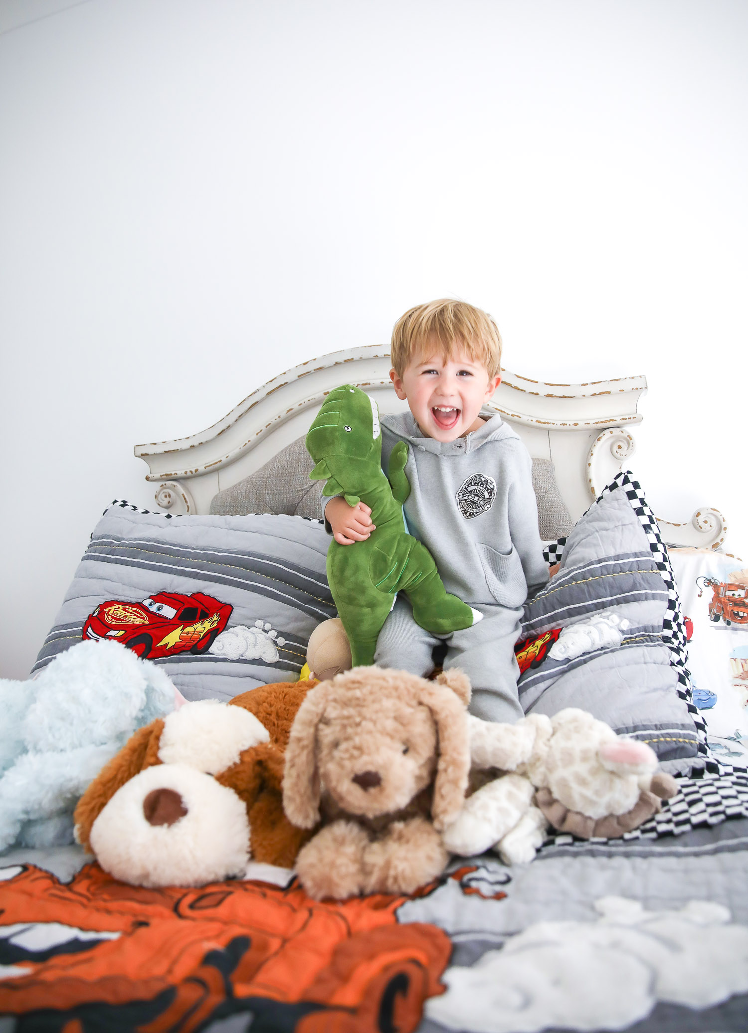 walmart kids home organization must haves, playroom organization ideas, emily gemma, the sweetest thing blog | Playroom Organization by popular US life and style blog, The Sweetest Thing: image of a little boy sitting on his bed with some stuffed animals.