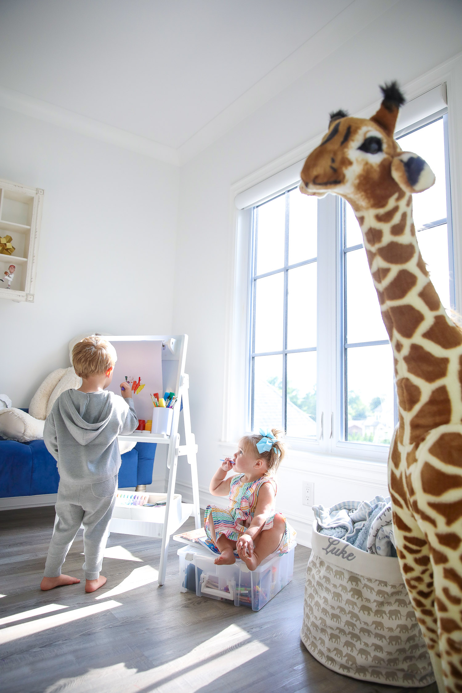 walmart kids home organization must haves, playroom organization ideas, emily gemma, the sweetest thing blog |Instagram Recap by popular US lifestyle blog, The Sweetest Thing: image of a young boy and girl in a play room with a Delta Children whiteboard, Humble Crew storage, Melissa and Doug giraffe, and ArtBin art container.