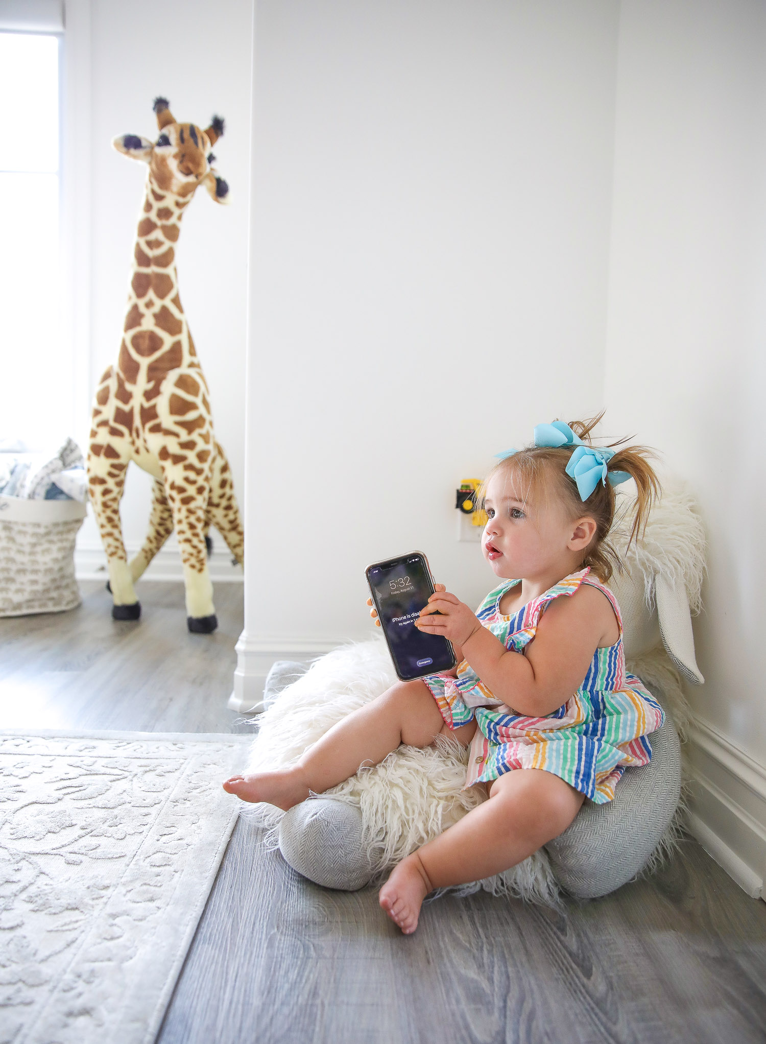 walmart kids home organization must haves, playroom organization ideas, emily gemma, the sweetest thing blog | Playroom Organization by popular US life and style blog, The Sweetest Thing: image of a little girl sitting on a floor pillow and holding a smartphone.