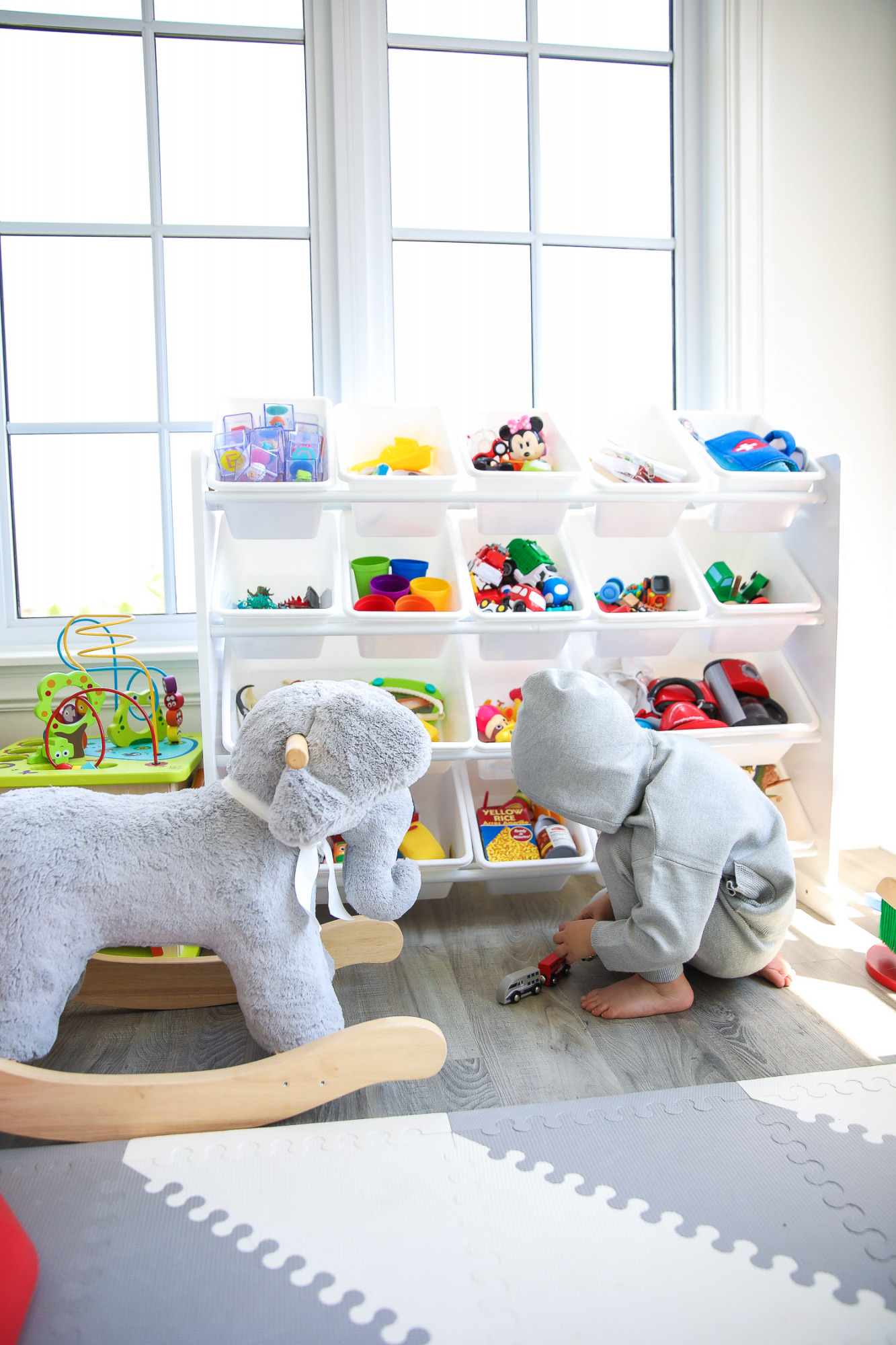 walmart kids home organization must haves, playroom organization ideas, emily gemma, the sweetest thing blog | Playroom Organization by popular US life and style blog, The Sweetest Thing: image of a playroom set up with a Walmart Humble Crew Super-Sized Toy Organizer with 16 Plastic Bins, foam flooring, basketball hoop, and rocking elephant.