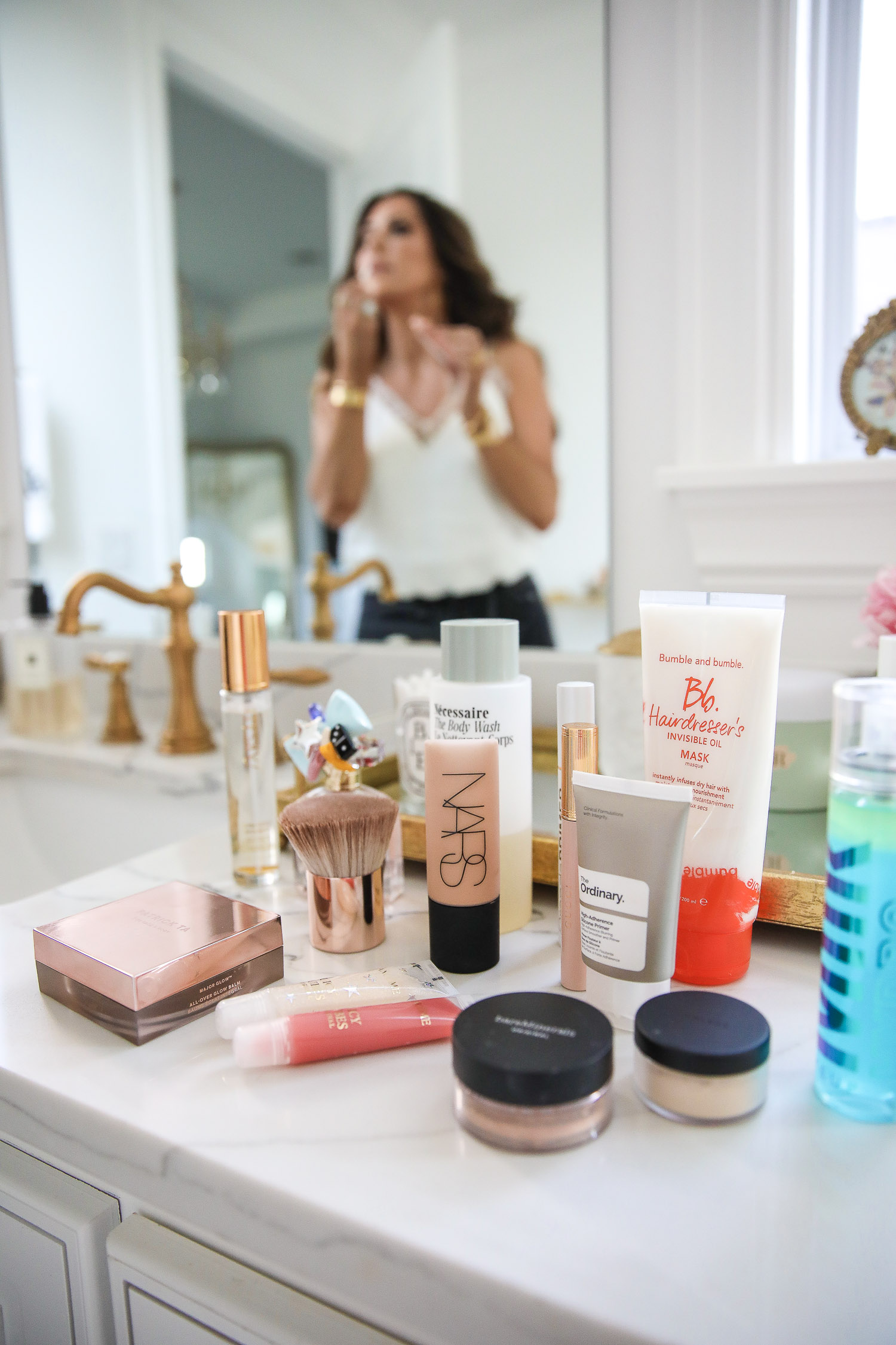 Sephora Favorites by popular US beauty blog, The Sweetest Thing: image of Nars foundation, The Ordinary primer, Bare Minerals powder, Milk makeup setting spray, lip gloss, and powder brush on a marble bathroom vanity counter.