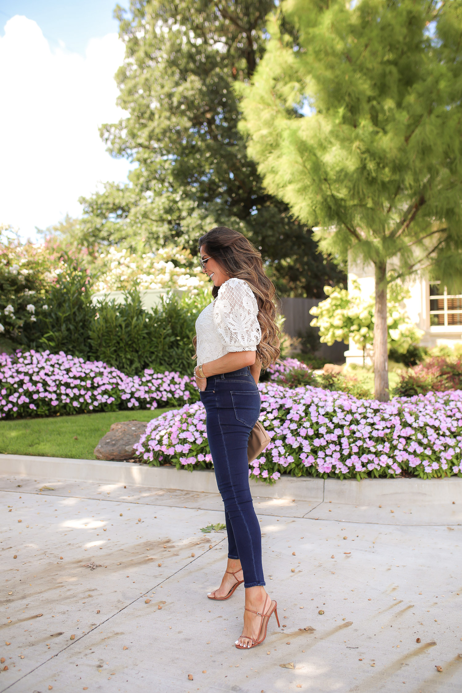 express fall 2020, express fall fashion trends 2020 pinterest, emily ann gemma, zimmermann dupe lookalike top, chloe dupe sunglasses | Fall Clothing by popular US fashion blog, The Sweetest Thing: image of Emily Gemma sitting down outside and wearing a Express Lace Puff Sleeve Top, Express High Waisted Luxe Comfort Knit Faded Skinny Jeans, Express Octagon Cut-Out Sunglasses, Express Thin Strap Textured Heels, Chanel earrings, and Cartier bracelets.