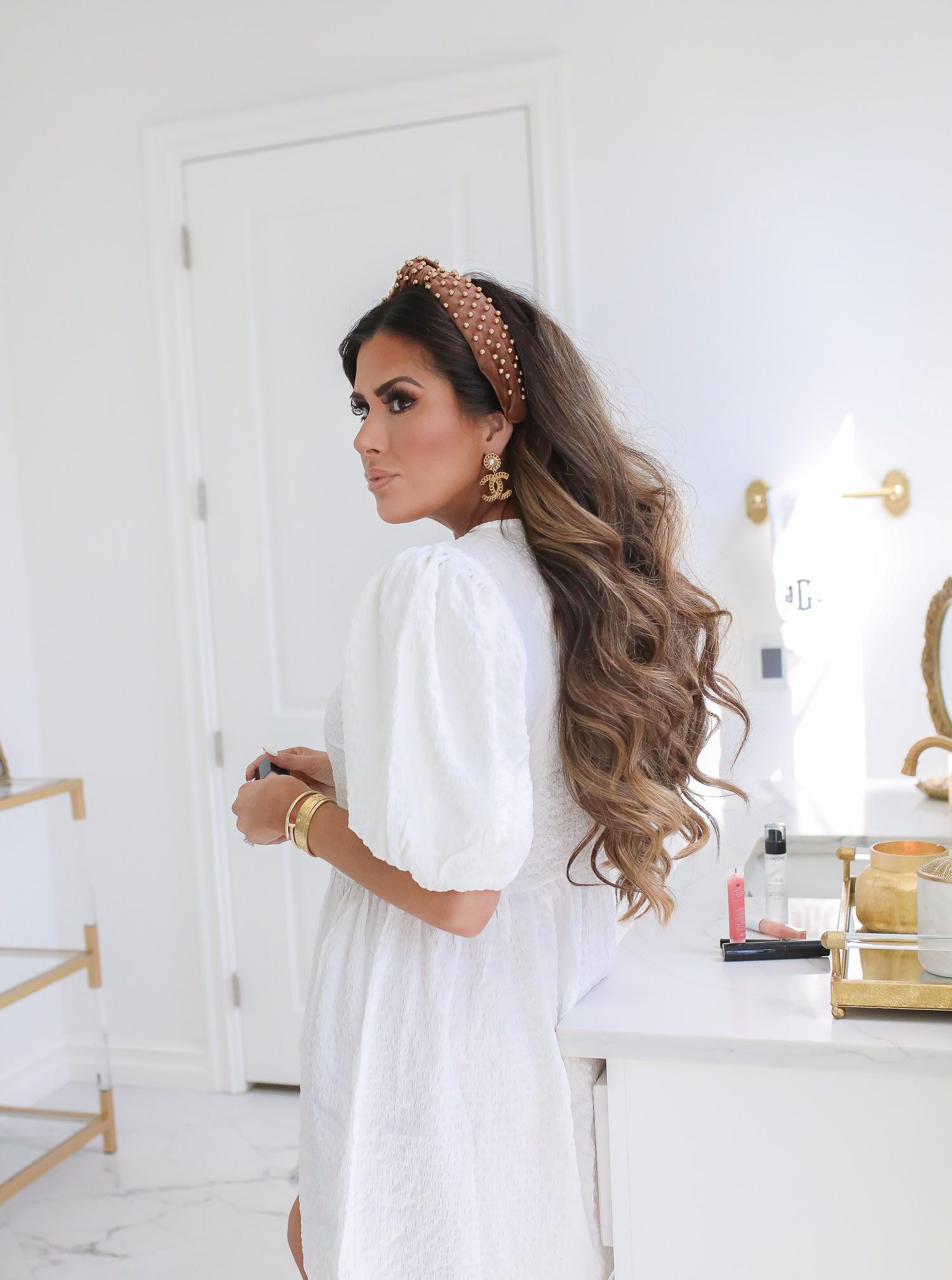 Lancôme Teint Idole Ultra Wear by popular US beauty blog, The Sweetest Thing: image of a woman wearing a white puff sleeve dress, Chanel earrings, and a pearl knot headband while holding a bottle of Lancome Teint Idole Ultra Wear foundation.