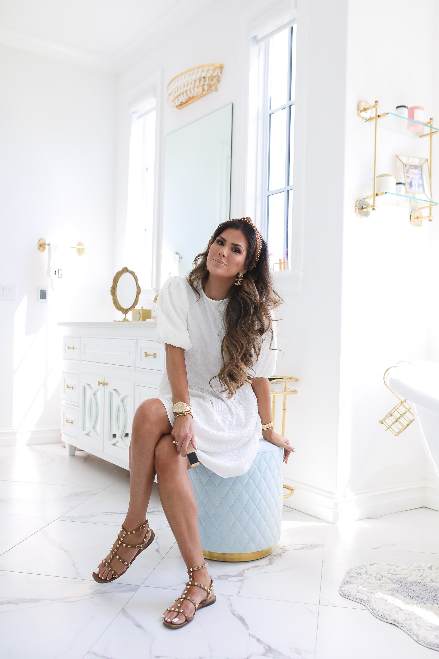 Lancôme Teint Idole Ultra Wear by popular US beauty blog, The Sweetest Thing: image of a woman wearing a white dress, pearl knot headband, stud sandals, and sitting on a blue tuft stool.