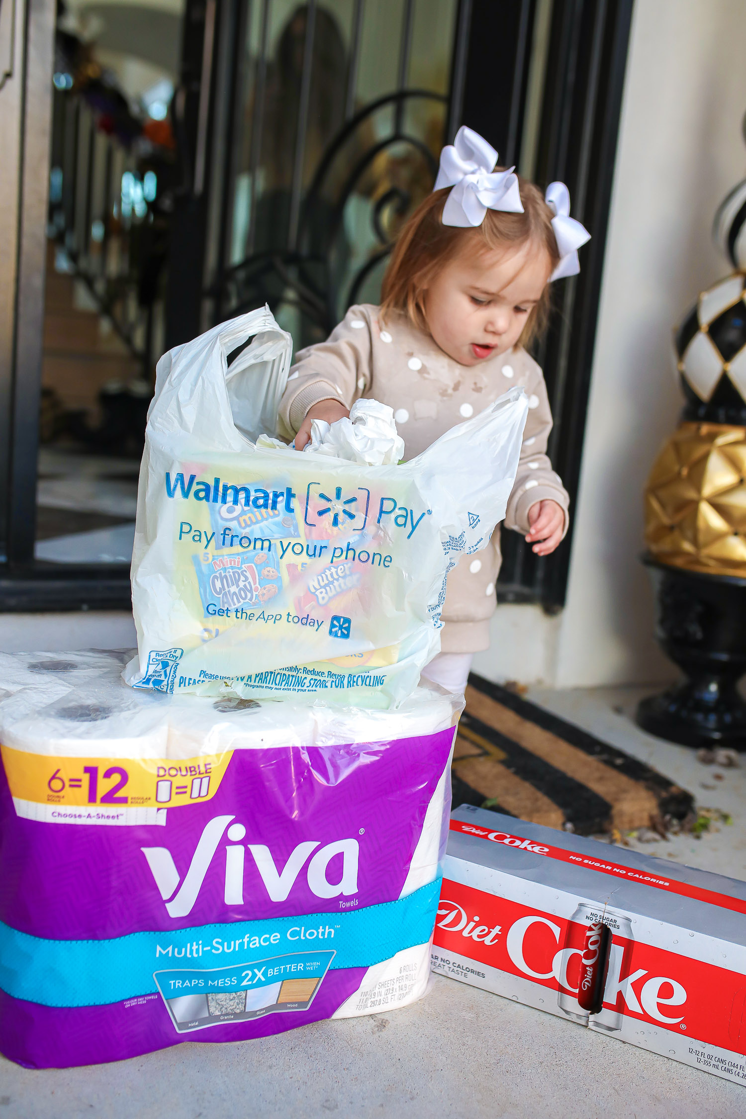walmart online pickup and delivery review, easiest way to order groceries online, walmart online grocery order, emily ann gemma | Walmart Grocery Pickup Faq by top US lifestyle blog, The Sweetest Thing: image of Emily Gemma's daughter Sophie standing on their front porch next to a package of VIva toilet paper and a case of Diet Coke.