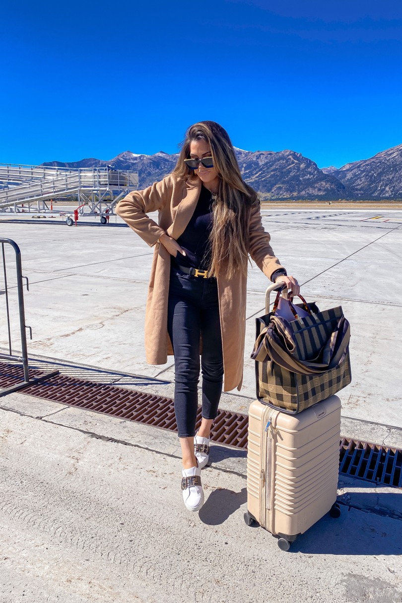 Instagram Recap by popular US lifestyle blog, The Sweetest Thing: image of Emily Gemma standing on a runway strip next to a Beis suitcase, and wearing Louis Vuitton sunglasses, Hermes belt, Bracha necklace, Good American jeans, Express coat and Fendi sneakers.