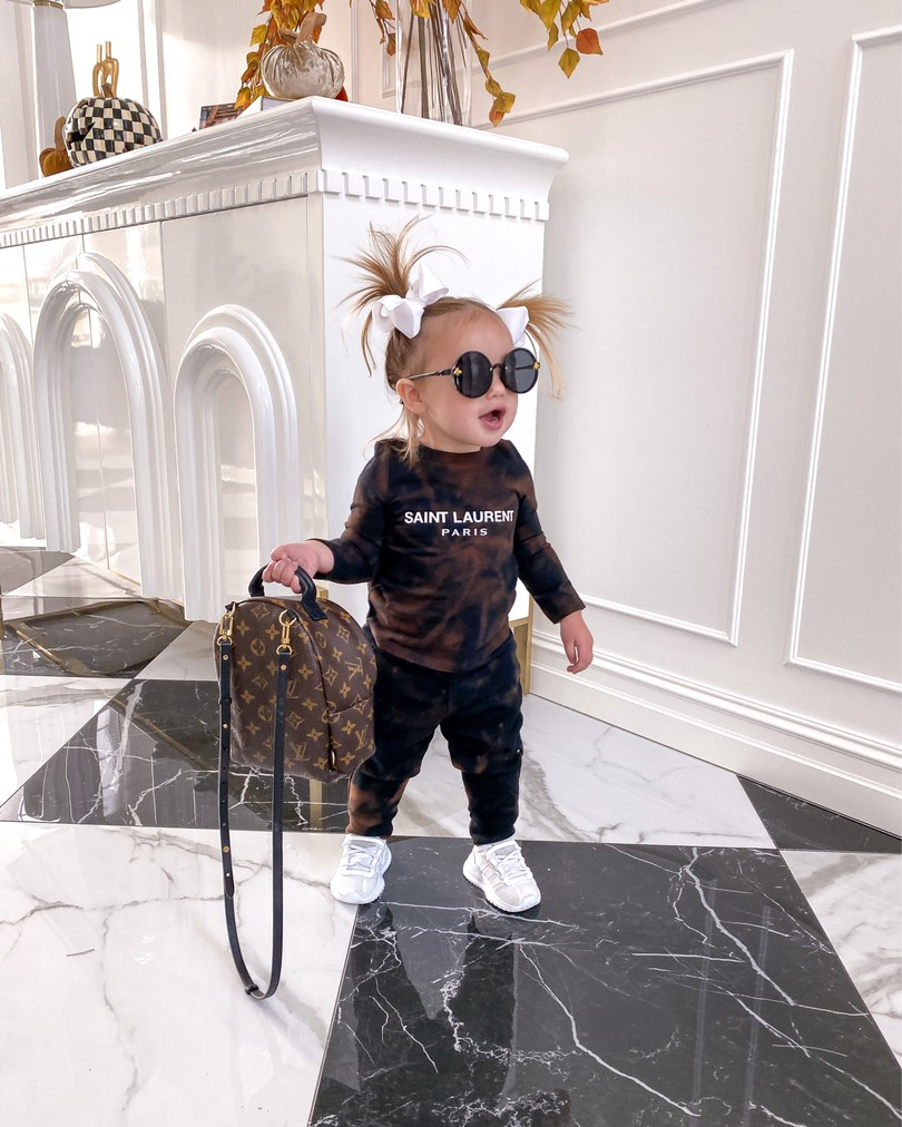 Instagram Recap by popular US lifestyle blog, The Sweetest Thing: image of Emily Gemma's daughter wearing a Nastik sweatsuit, white sneakers, white hair bows and holding a Louis Vuitton backpack.