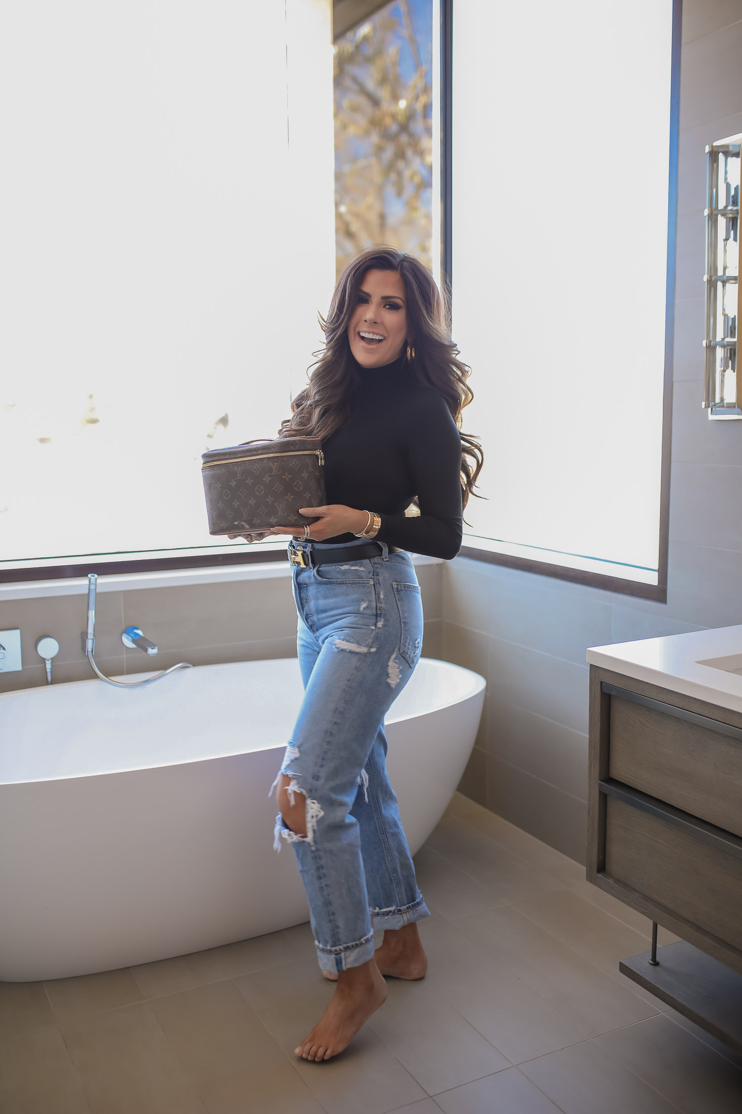 Sephora savings event fall 2020, sephora VIB sale event, beauty blogger sephora favorites fall 2020, emily ann gemma-6 |Sephora Beauty Insider Sale by popular US beauty blog, The Sweetest Thing: image of Emily Gemma wearing a black turtle neck and distressed jeans and holding a Louis Vuitton makeup case in bathroom with a modern white soaking tub.